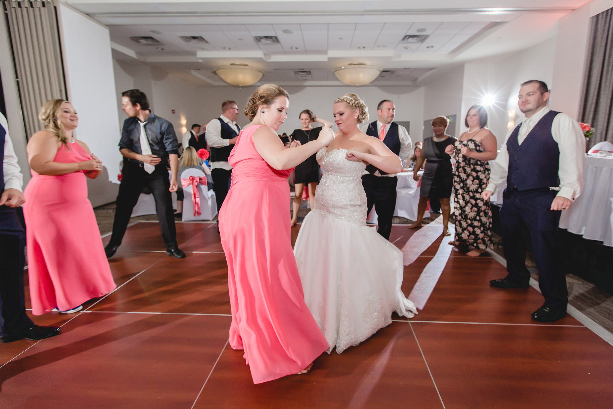 Bride dances with her bridesmaid at the Pittsburgh Airport Marriott