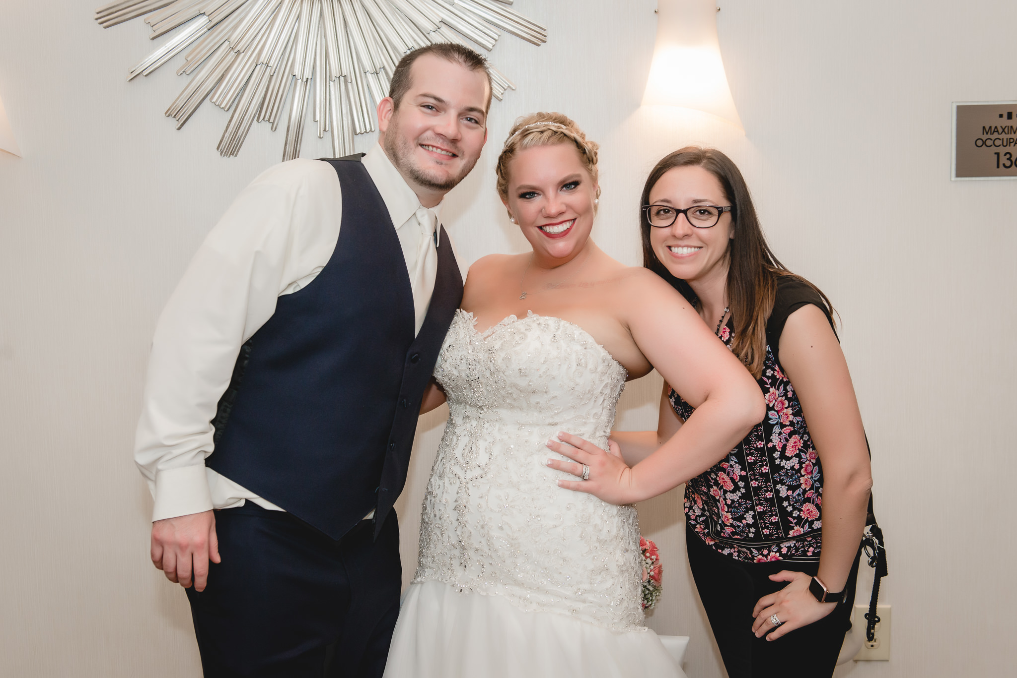 Bride and groom pose with their photographer at the Pittsburgh Airport Marriott