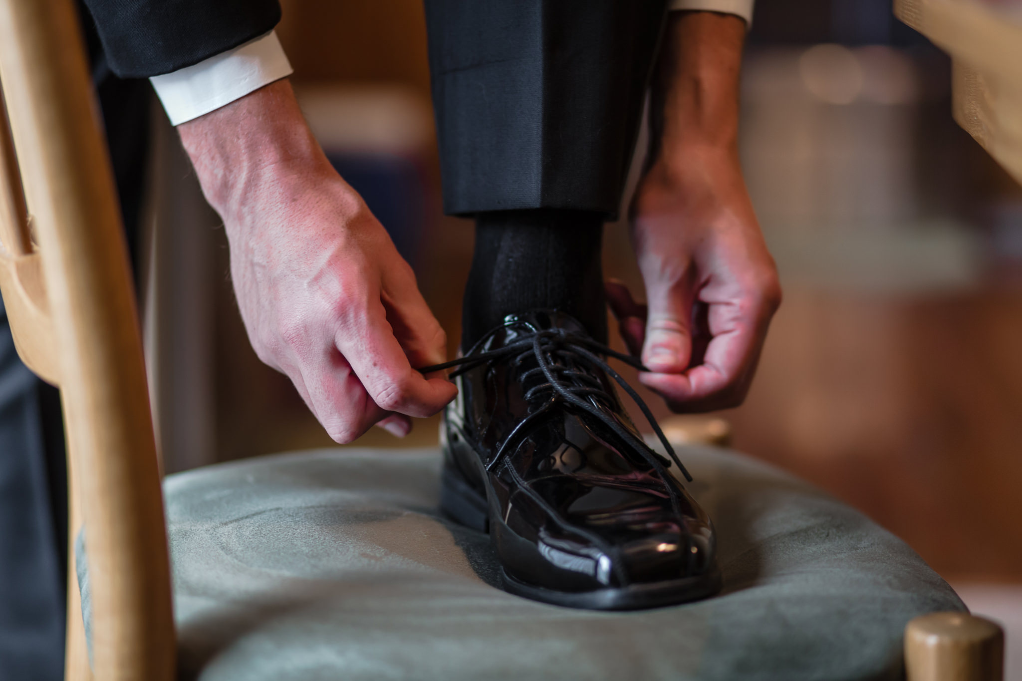 Groom ties his shoe before his Gathering Place at Darlington Lake wedding ceremony
