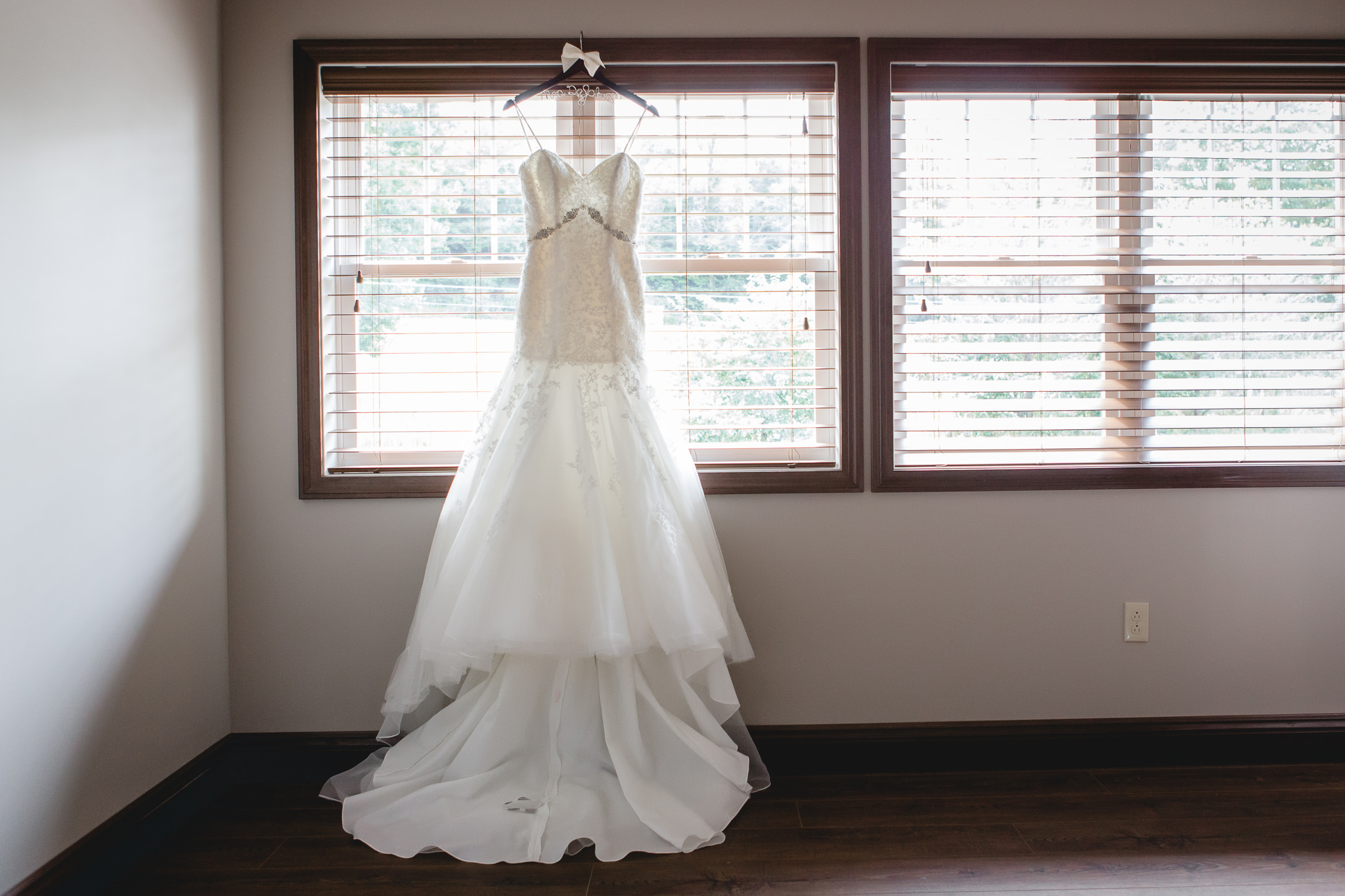 Alfred Angelo bridal gown hangs from a window before a wedding at the Gathering Place at Darlington Lake