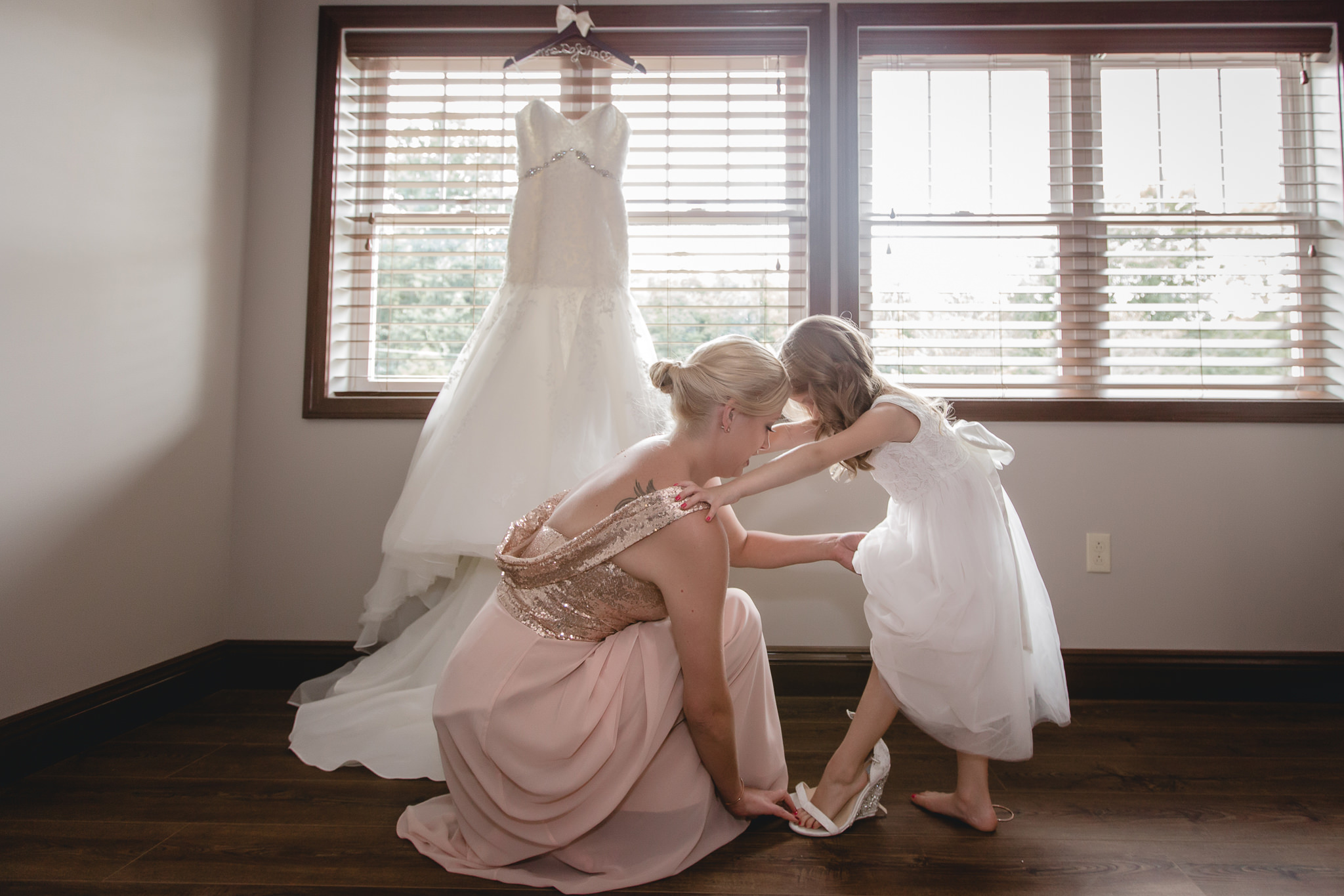 Flower girl tries on the bride's wedding shoes