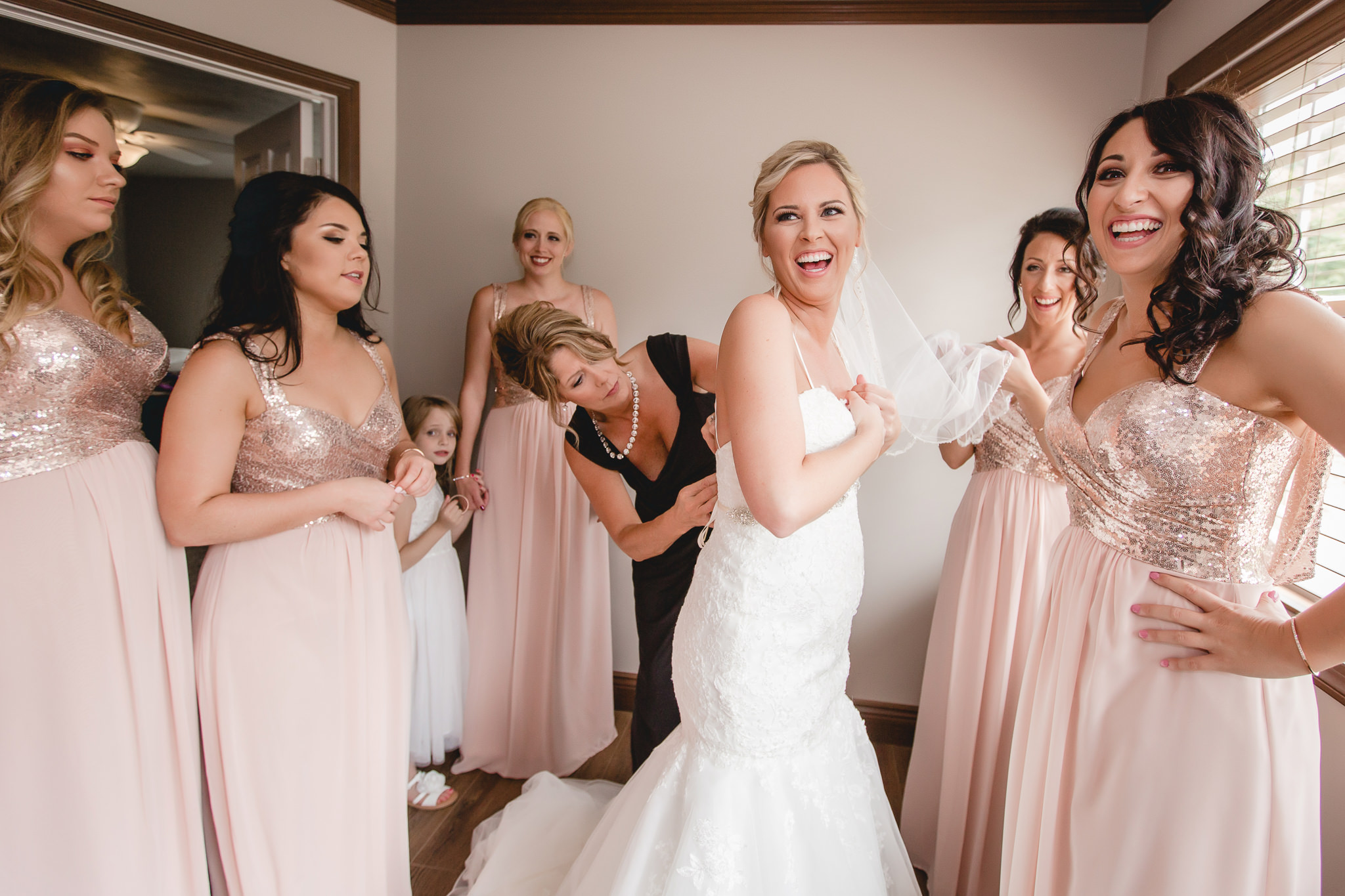 Bride laughs with her bridesmaids as she gets dressed for her Gathering Place at Darlington Lake wedding