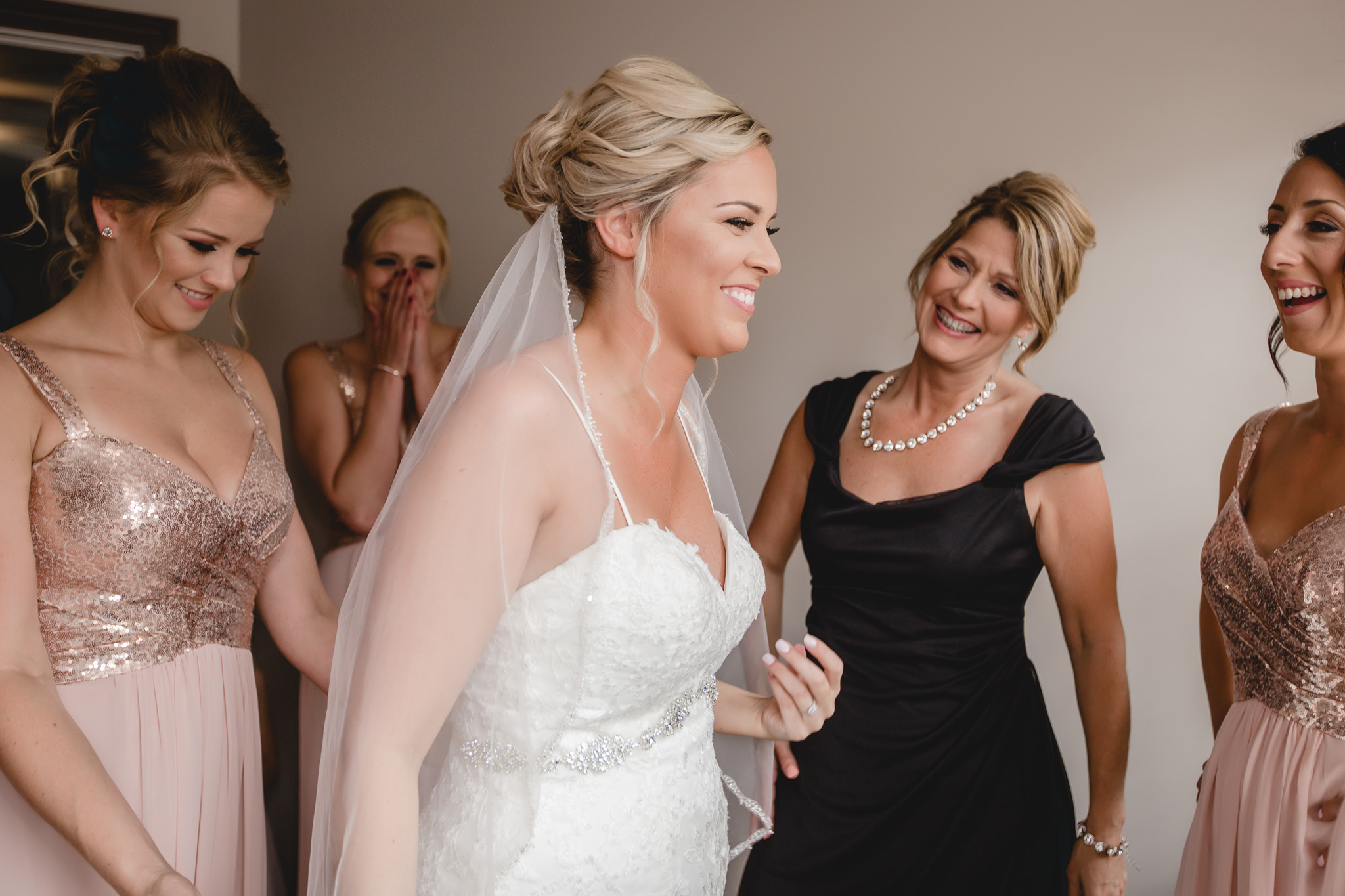 Mother of the bride smiles as her daughter gets into her wedding dress