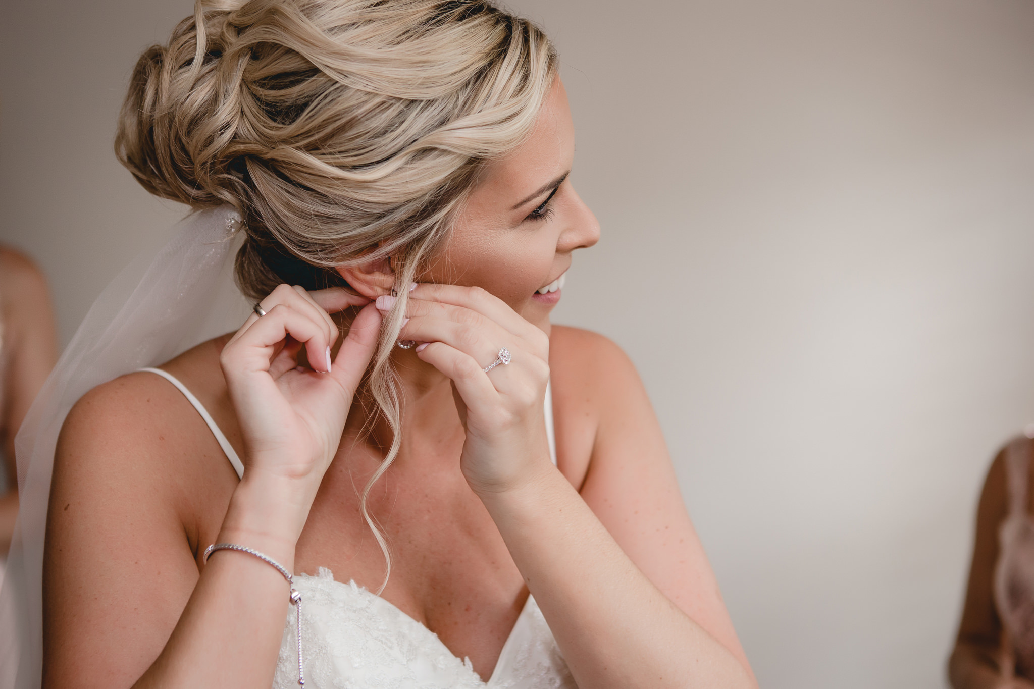 Bride puts on her earrings before her Gathering Place at Darlington Lake wedding