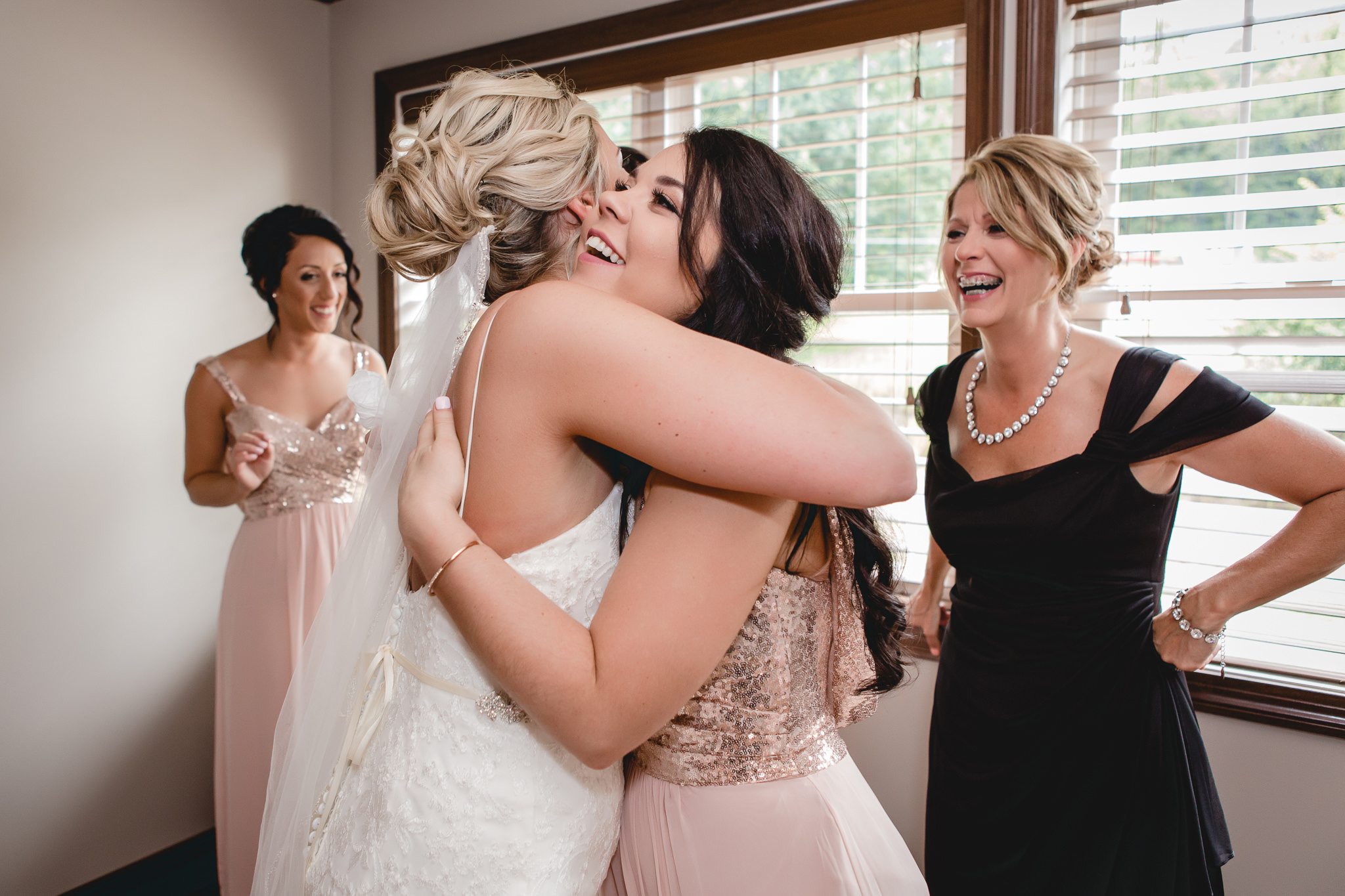Bride hugs her bridesmaid before her wedding at the Gathering Place at Darlington Lake