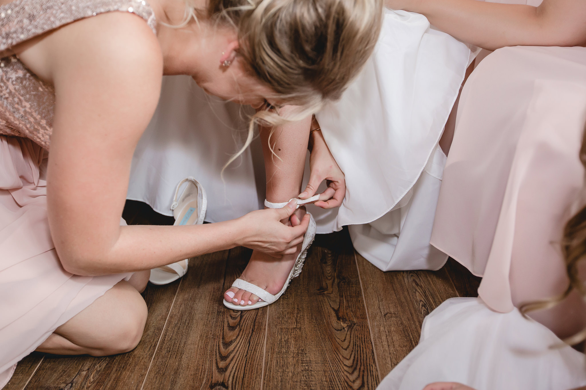 Maid of honor helps the bride into her shoes before her wedding at the Gathering Place at Darlington Lake