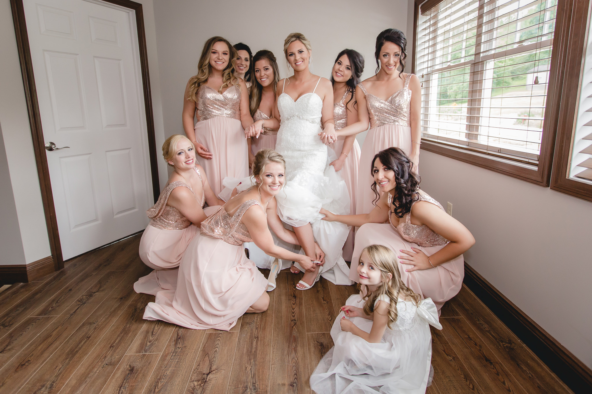 Bridesmaids pose as they help the bride into her shoes