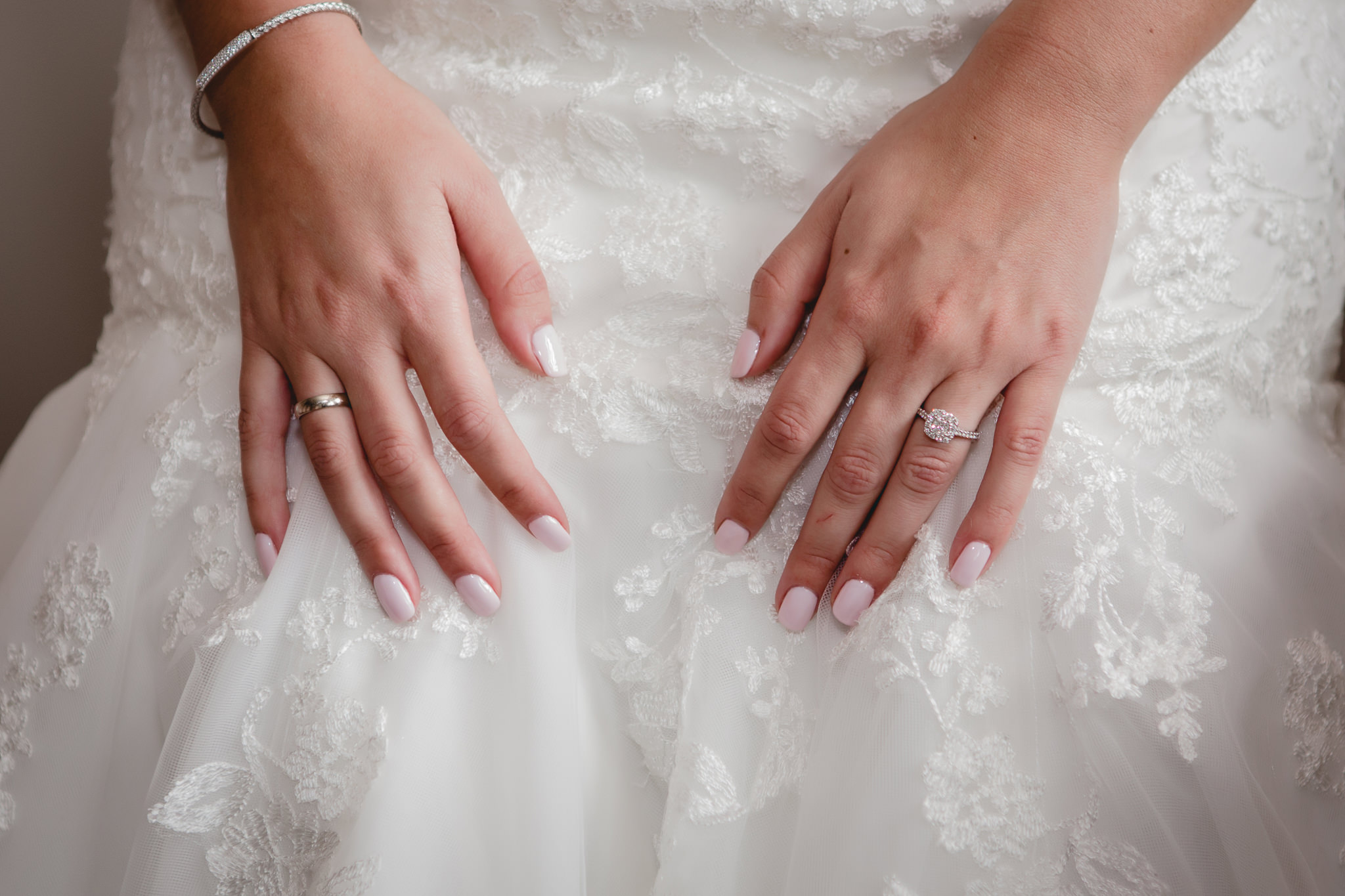Closeup of bride's hands on her lace wedding dress