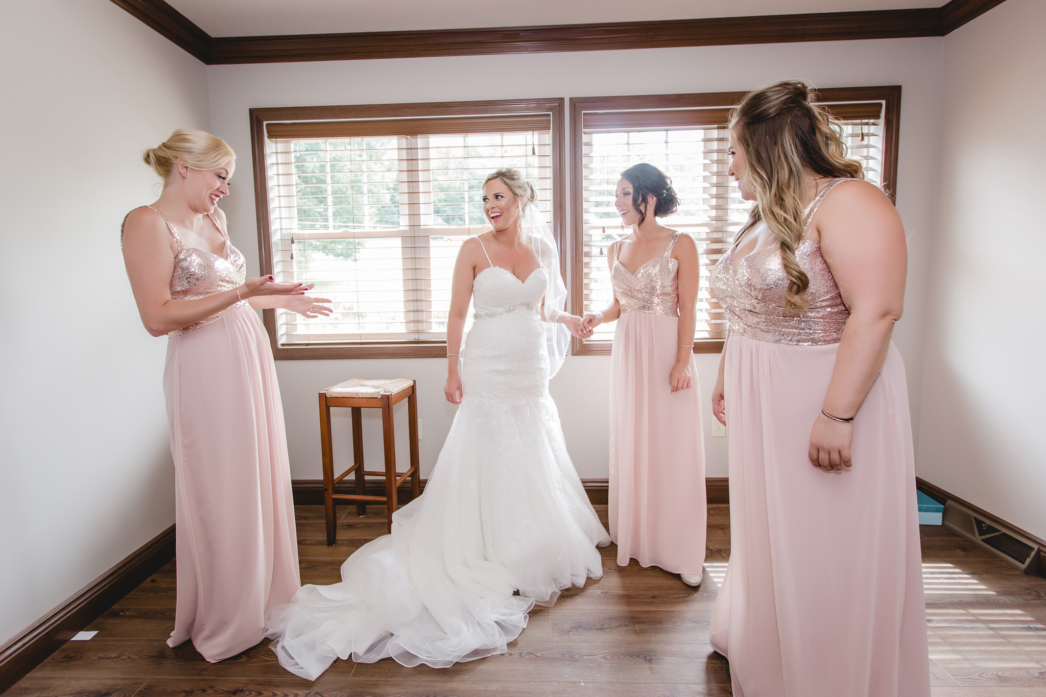 Bride smiles as her bridesmaids see her in her dress