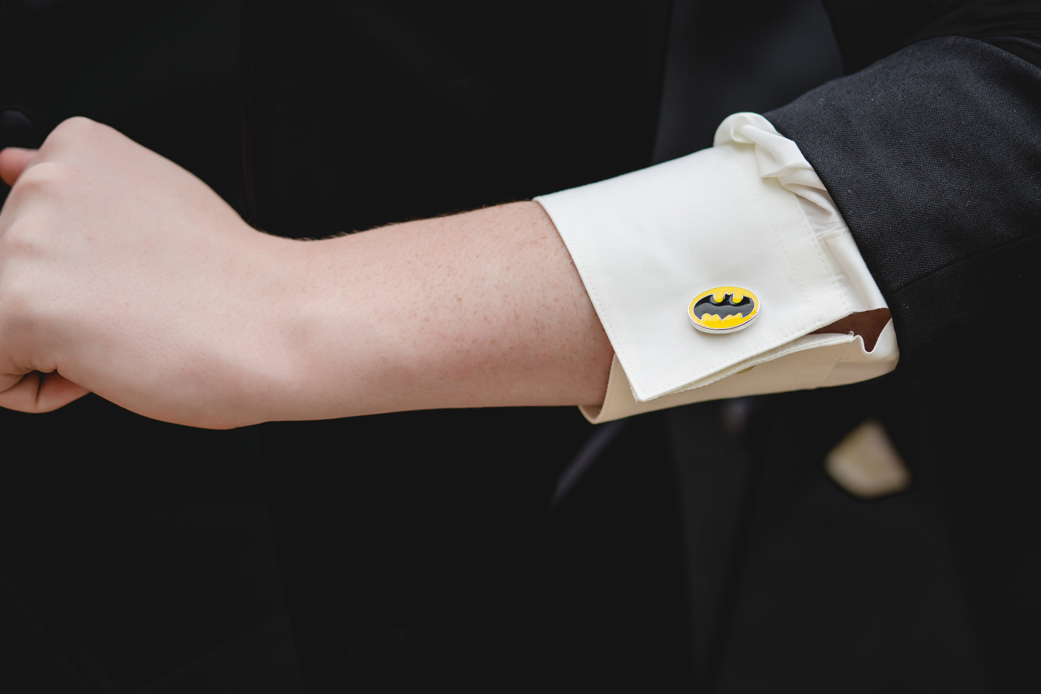 Groom shows off his Batman cufflinks before his Gathering Place at Darlington Lake wedding