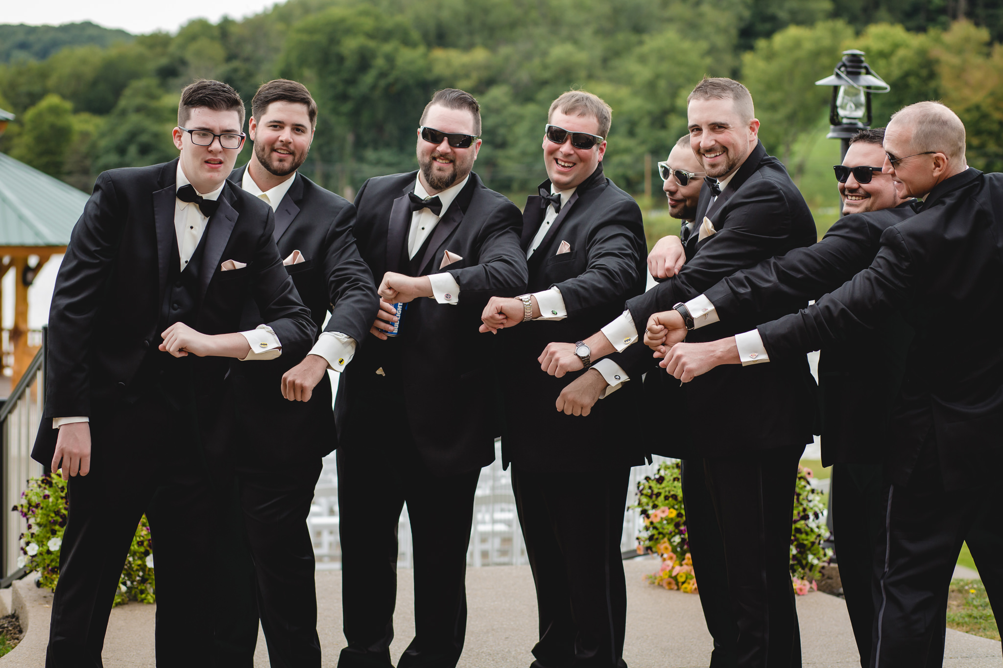 Groomsmen show off their super hero cufflinks at the Gathering Place at Darlington Lake