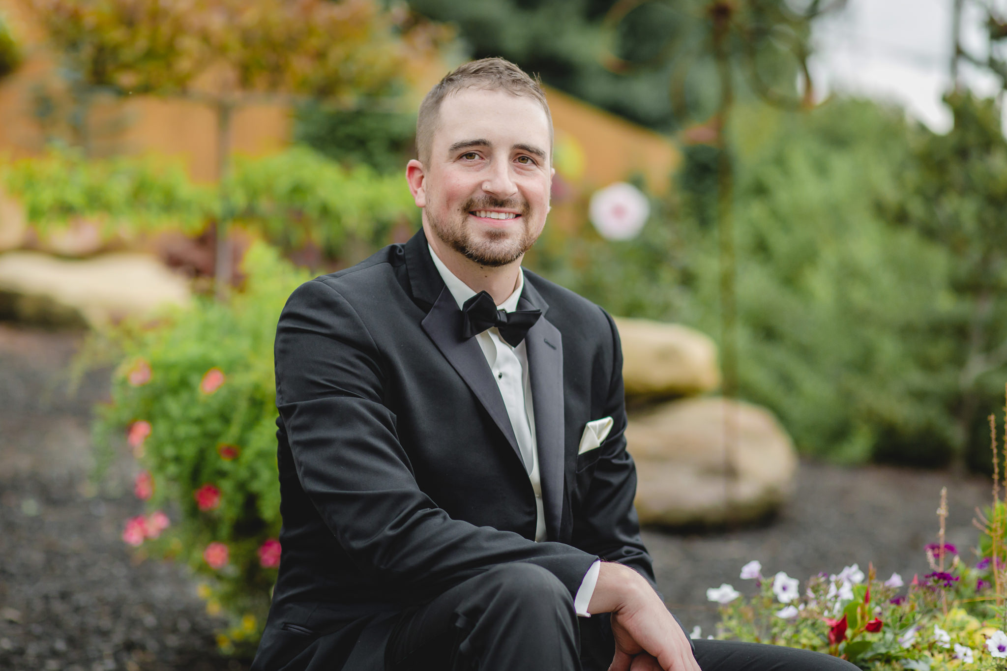 Groom poses in the garden at the Gathering Place at Darlington Lake