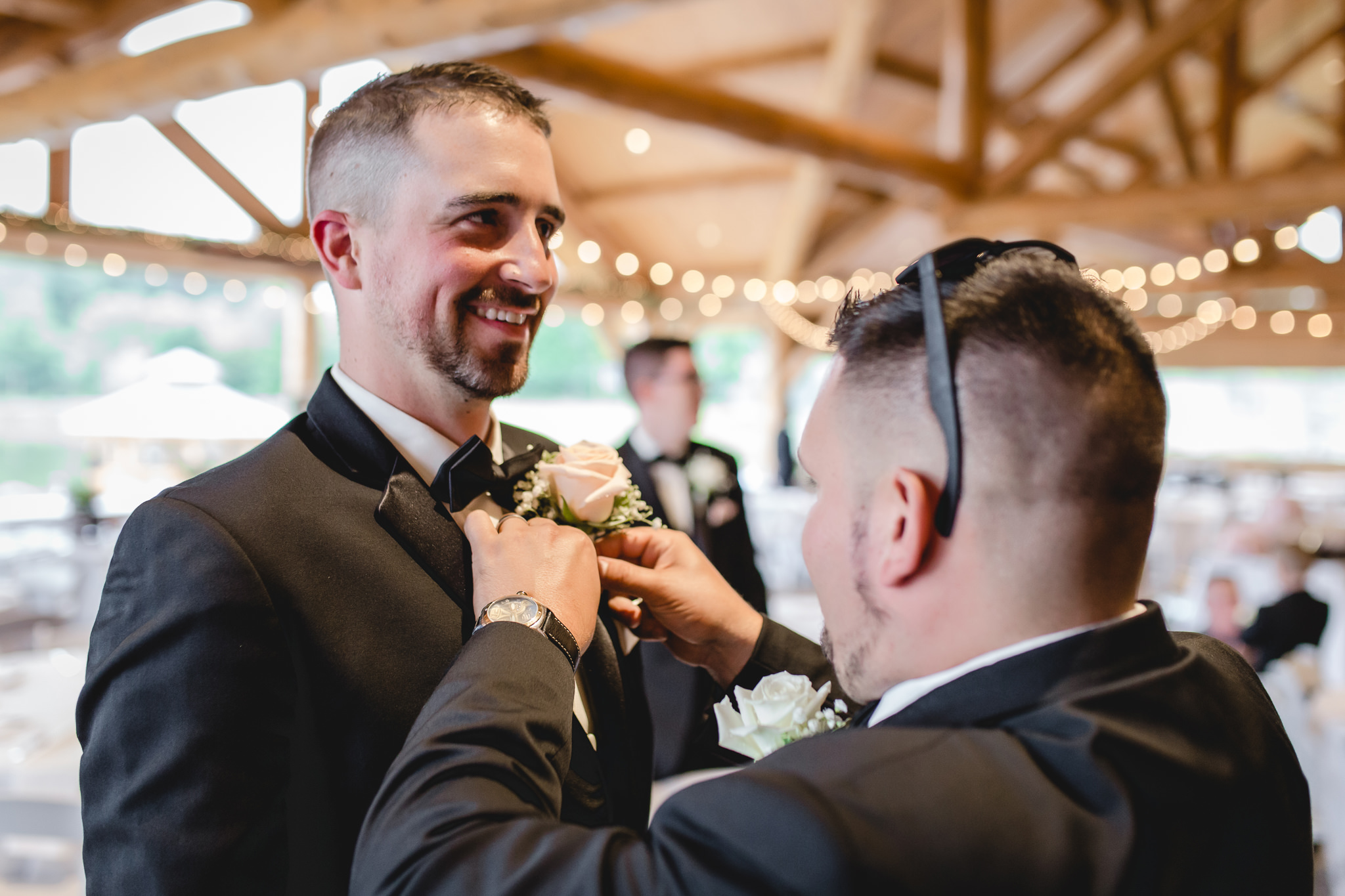 Groomsman fixes the groom's boutonniere at the Gathering Place at Darlington Lake