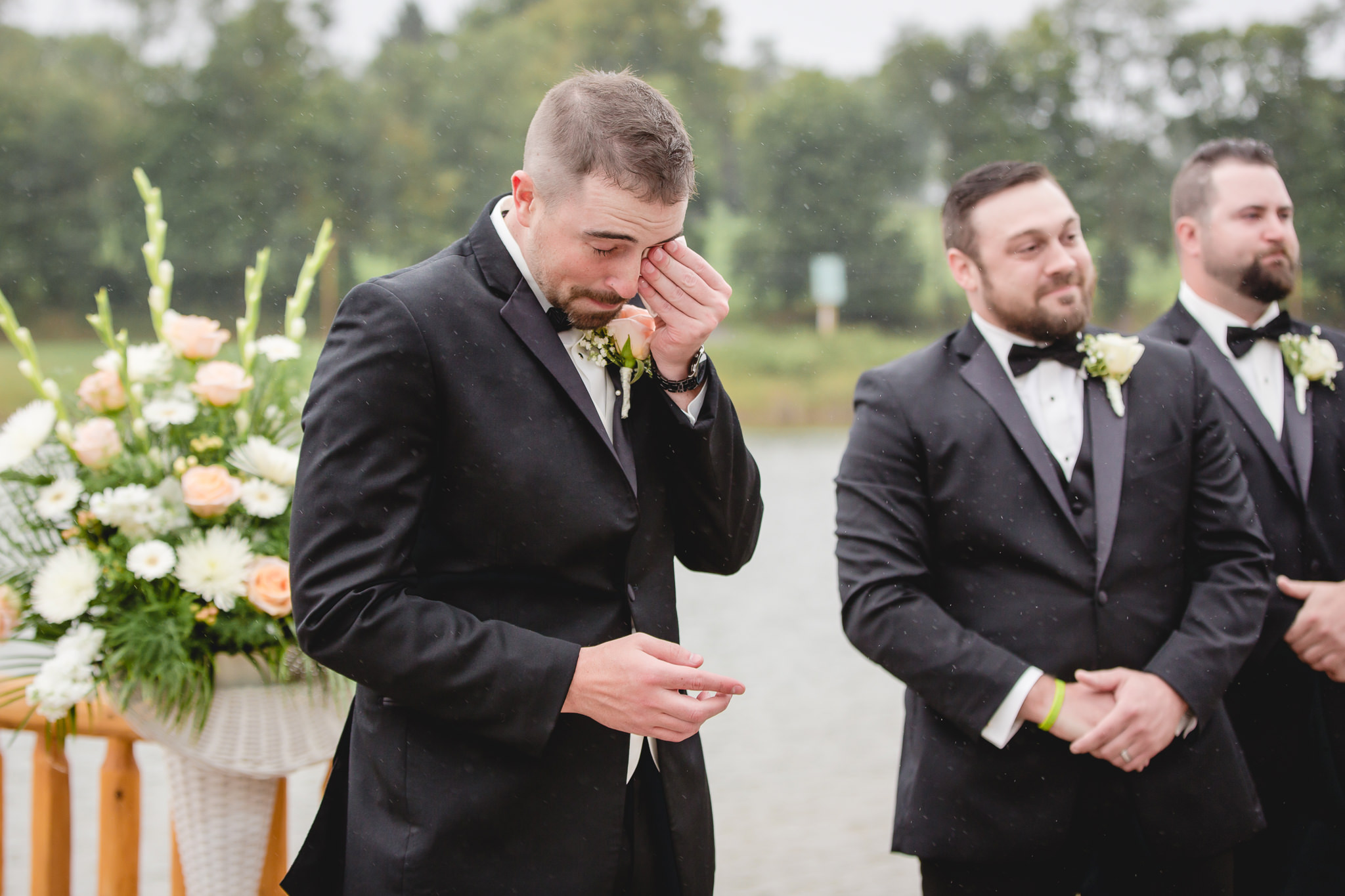 Groom wipes away tears as his bride walks down the aisle at the Gathering Place at Darlington Lake