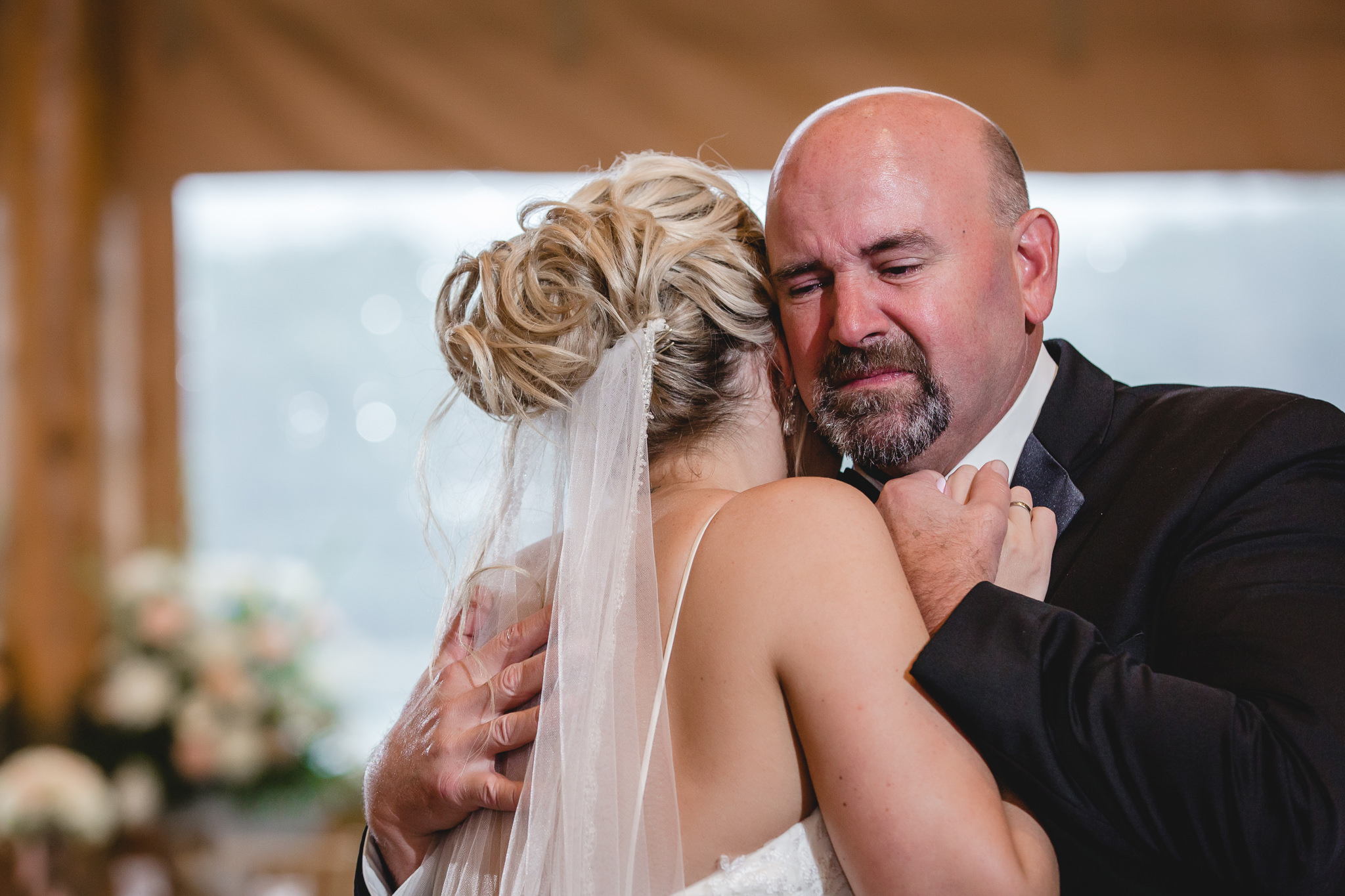 Father of the bride cries while dancing with his daughter at the Gathering Place at Darlington Lake
