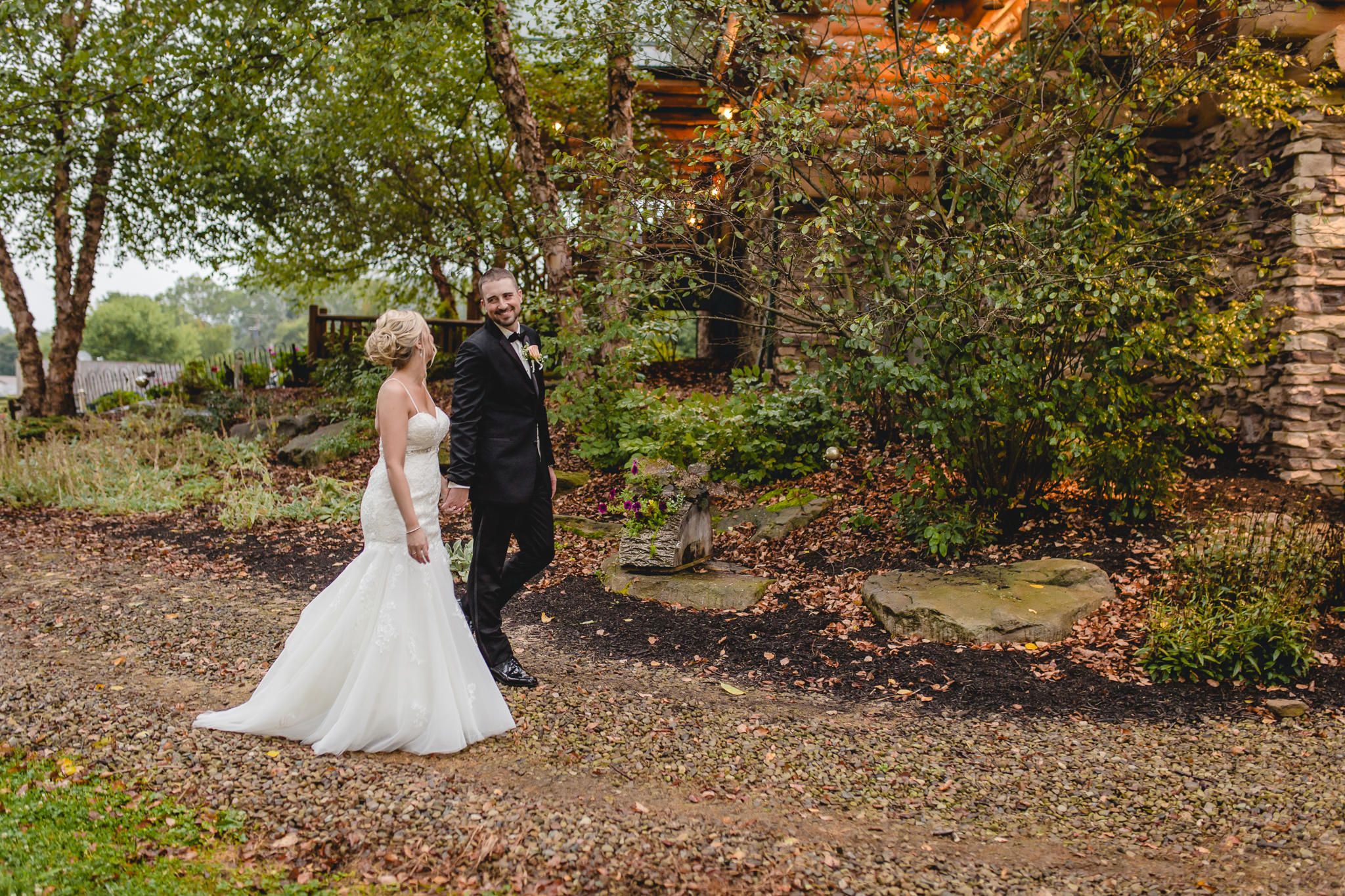 Bride and groom walk around the cabin at the Gathering Place at Darlington Lake