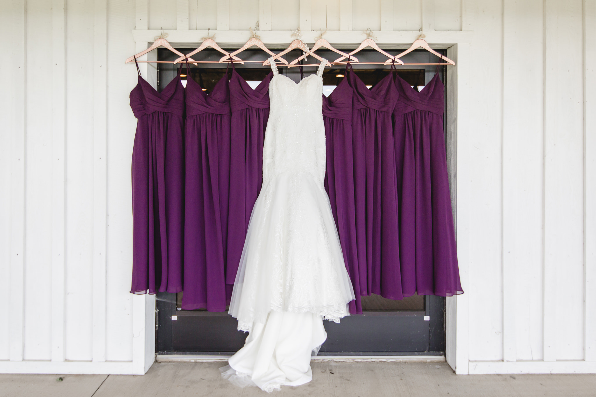 Wedding dress hangs with bridesmaids dresses at White Barn
