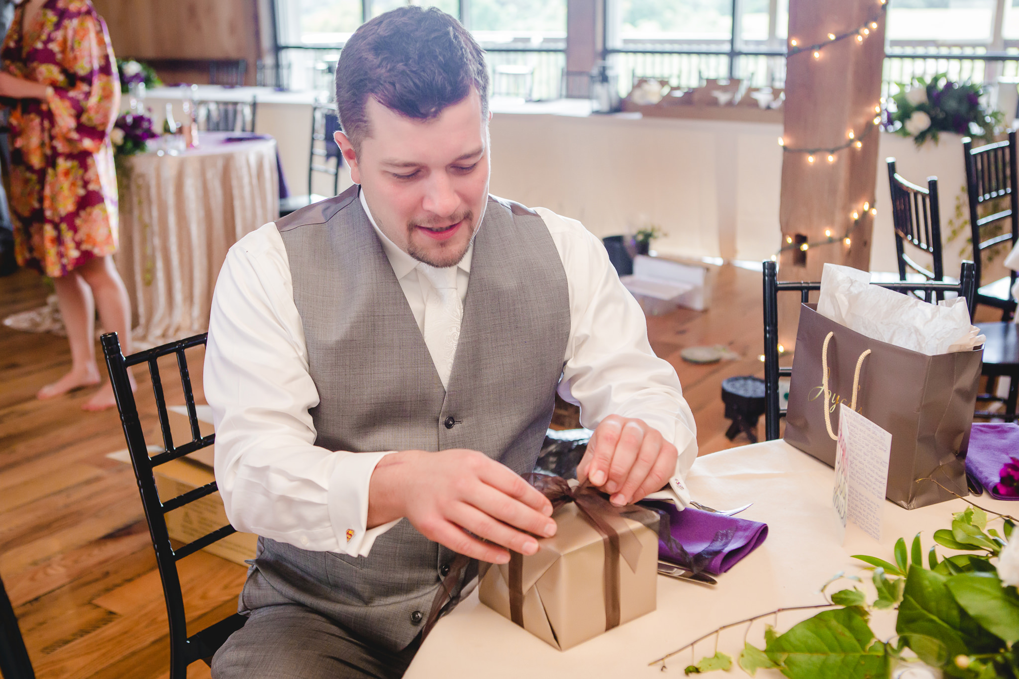 Groom opens a present from the bride at White Barn