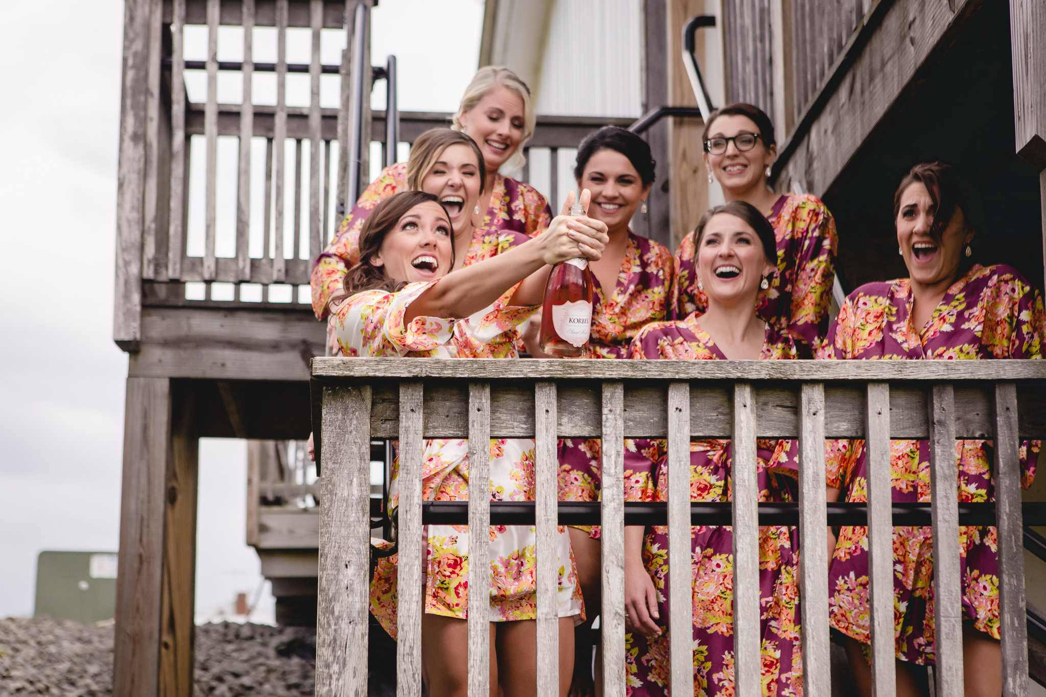 Bride pops a champagne bottle with her bridesmaids at White Barn