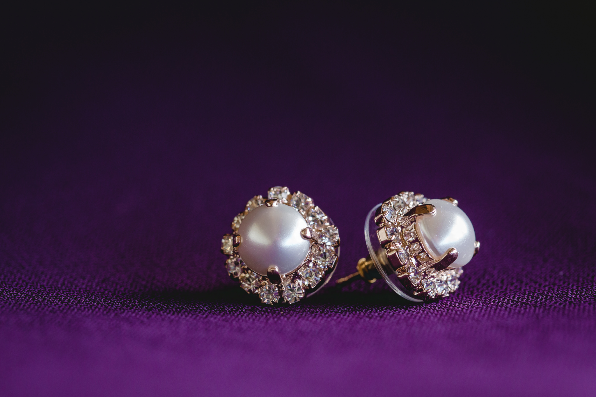 Rose gold and pearl earrings on a purple bridesmaids dress