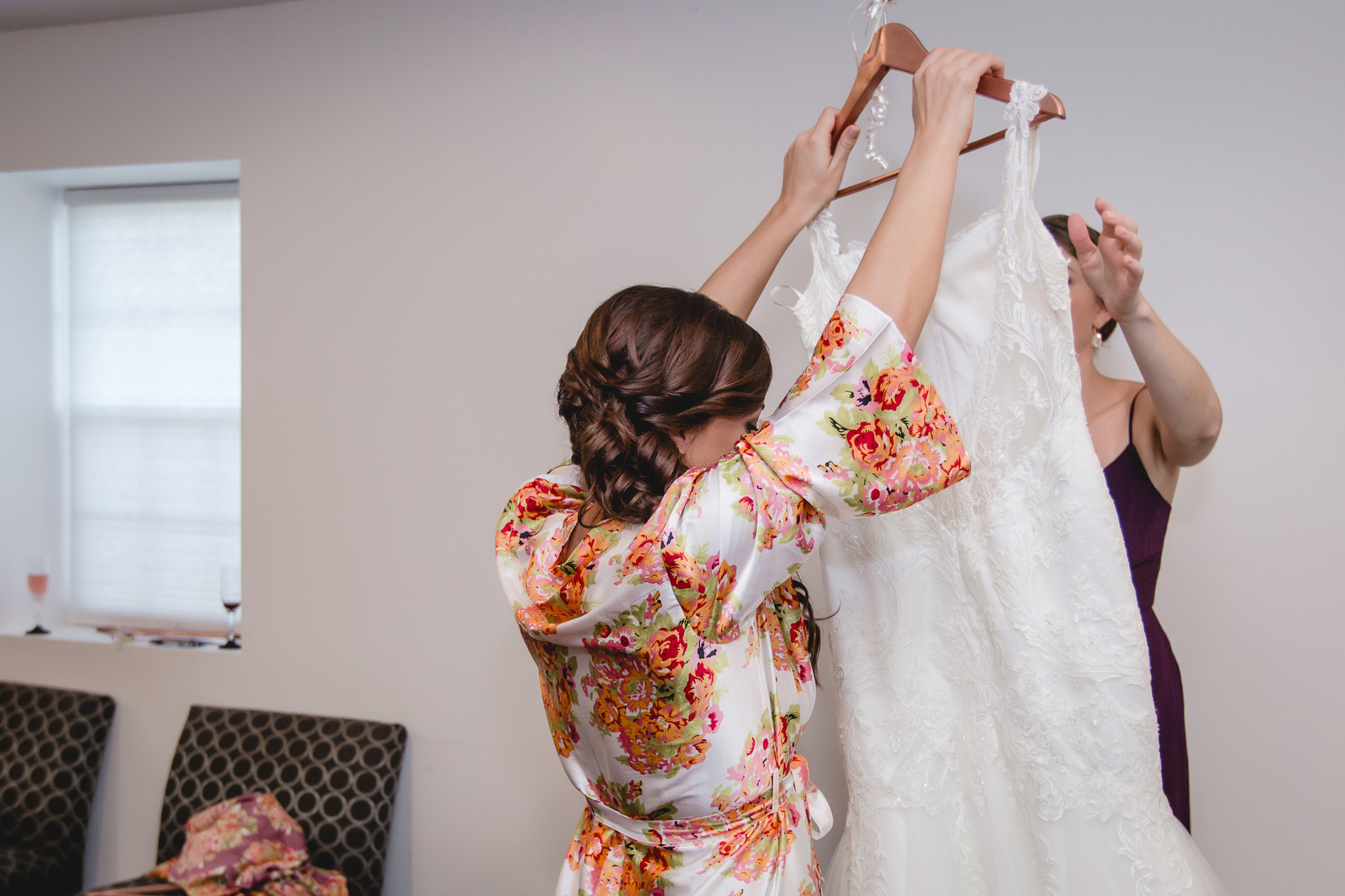 Bride takes her wedding dress off the hanger at White Barn