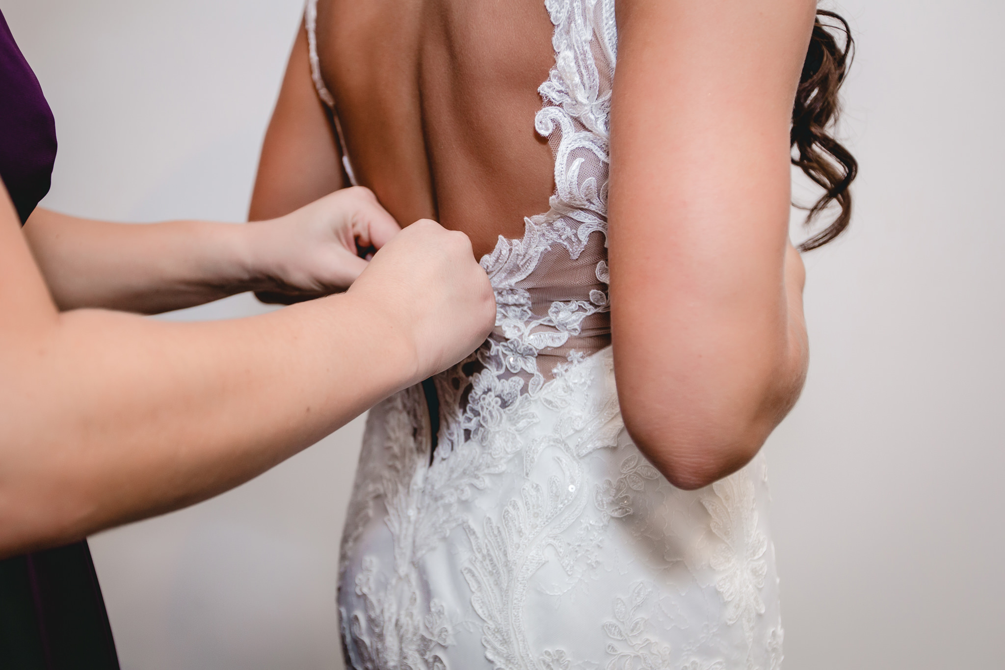 Bridesmaid zips the bride's dress before her wedding ceremony at White Barn