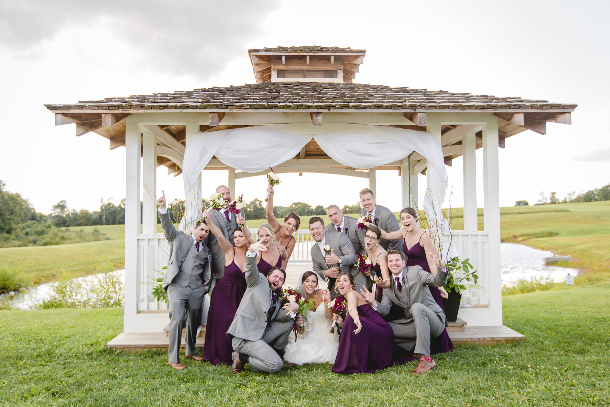 Bridal party being goofy in front of the gazebo at White Barn