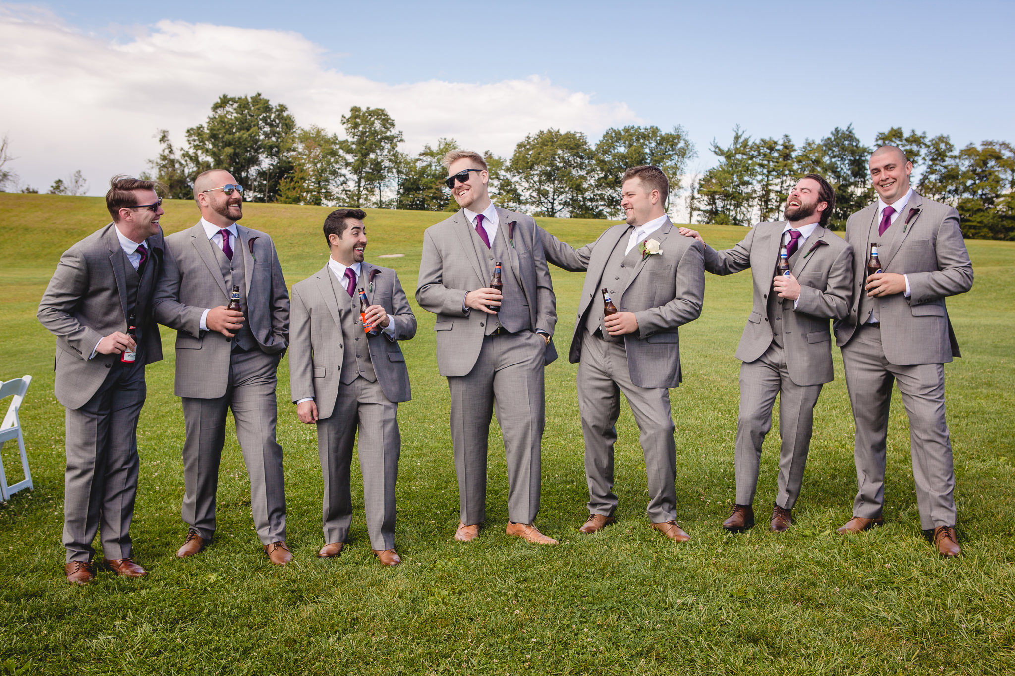 Groom and groomsmen laugh and drink beer before a White Barn wedding ceremony
