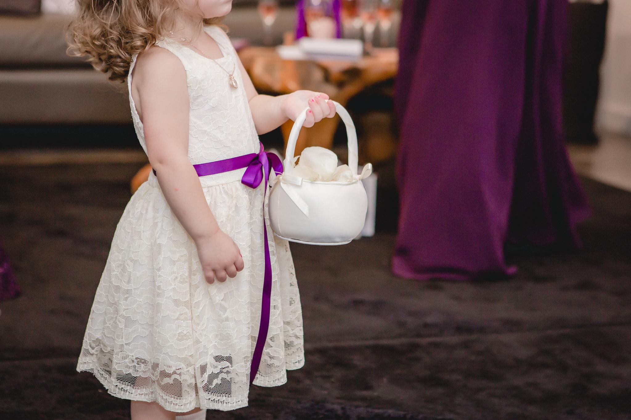 Flower girl holds her basket at the White Barn