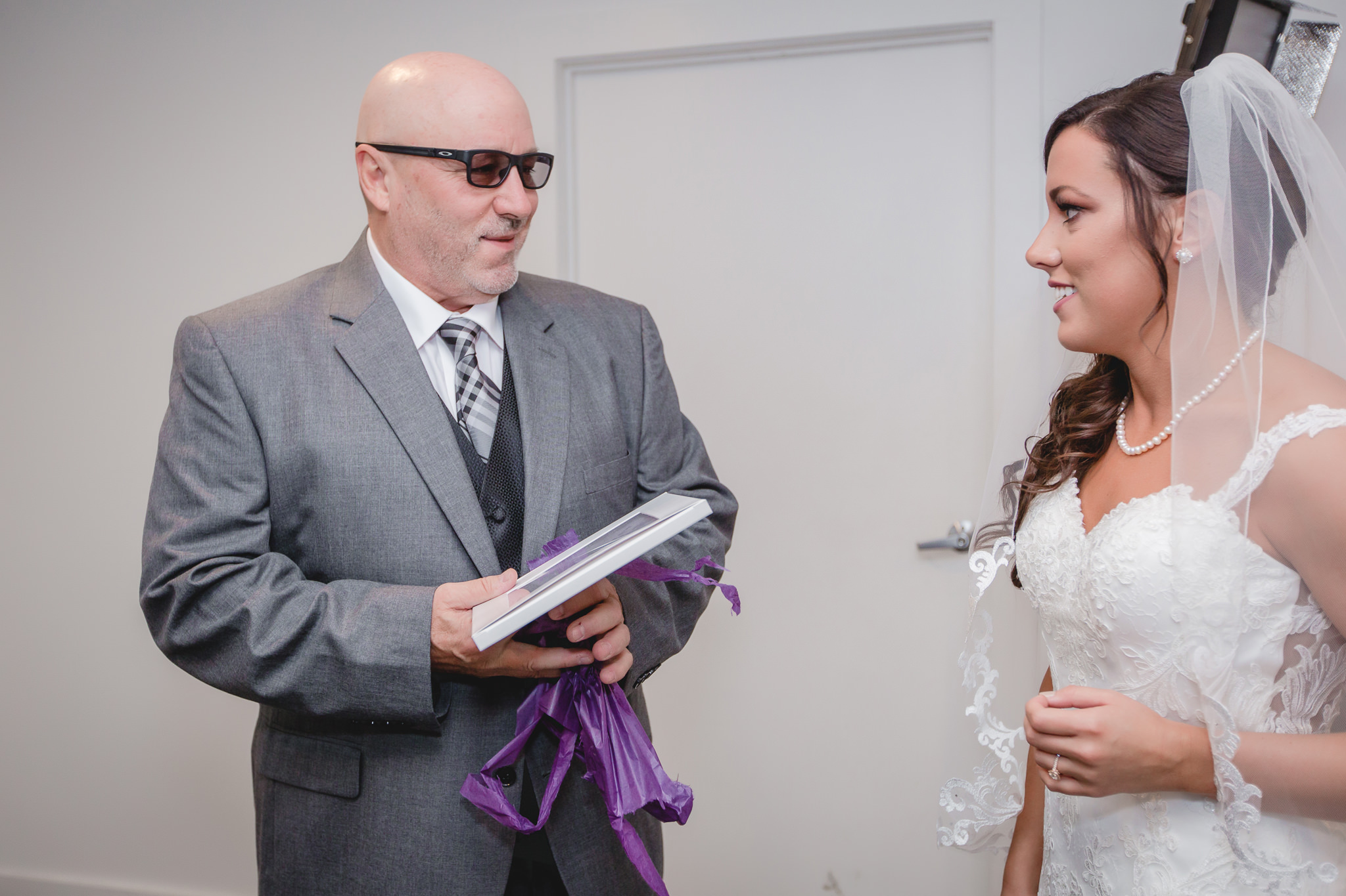 Father of the bride opens a gift from the bride at White Barn