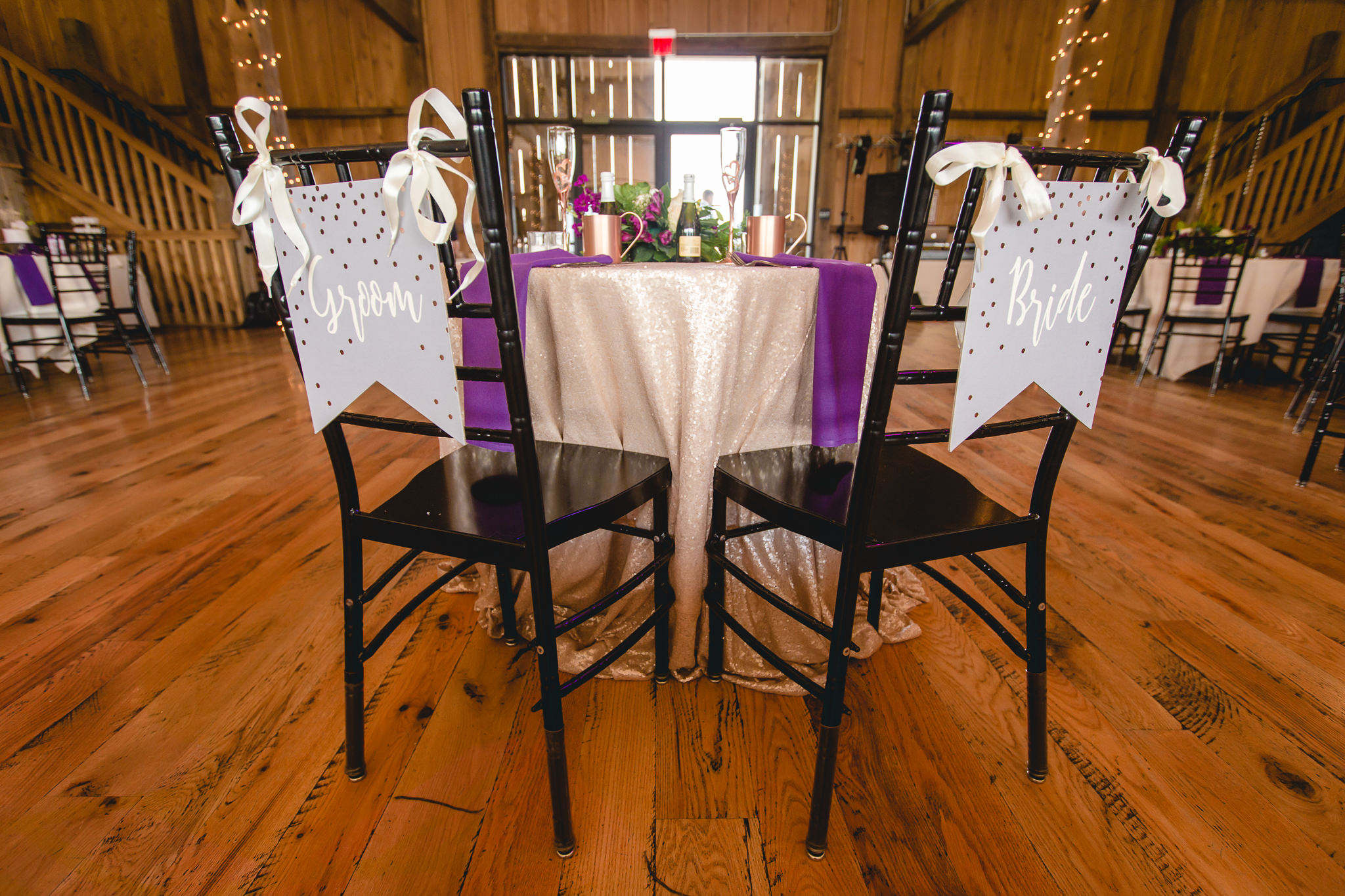 Groom and Bride signs on the sweetheart table chairs at White Barn