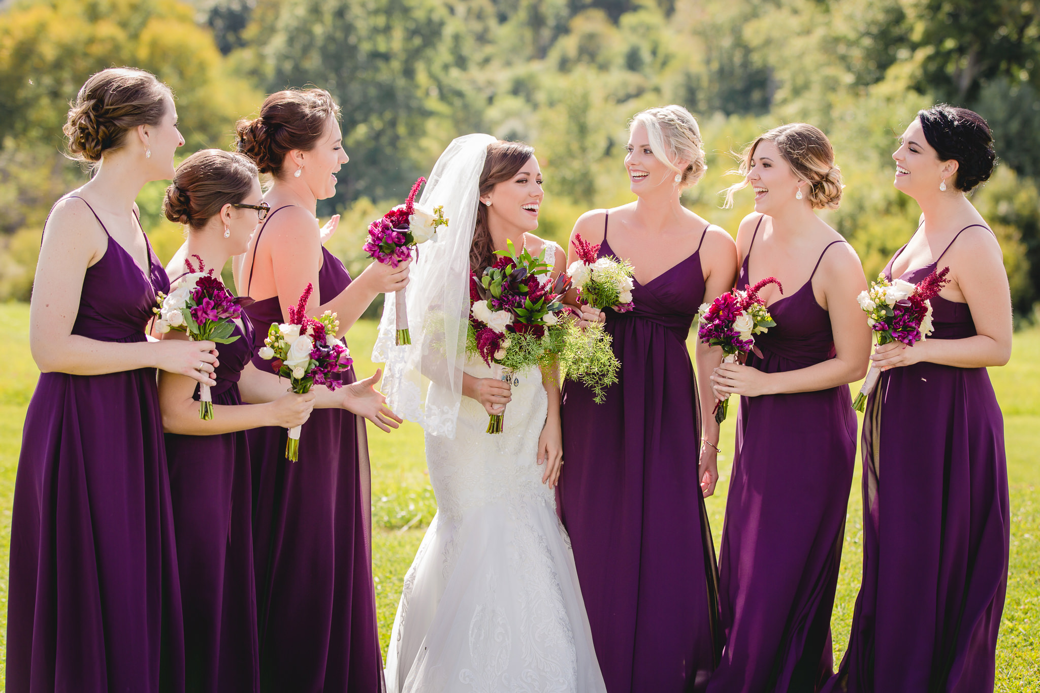 Bride laughs with her bridesmaids outside at White Barn in Prospect PA