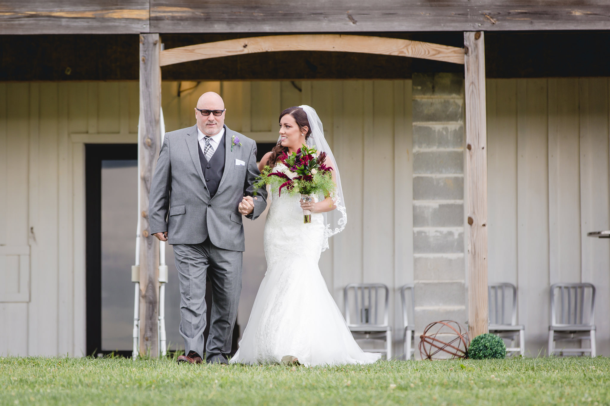 Bride walks down the aisle with her father at White Barn
