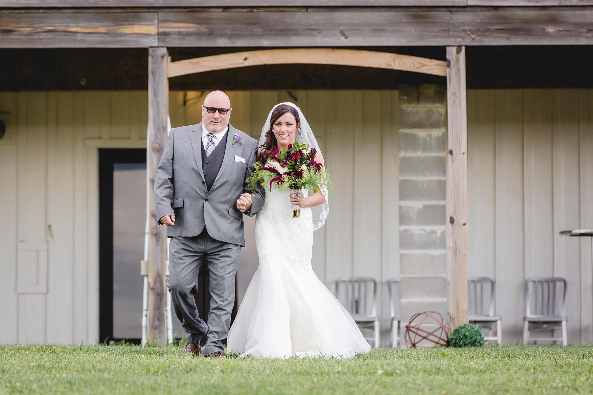 Father of the bride walks his daughter down the aisle at White Barn