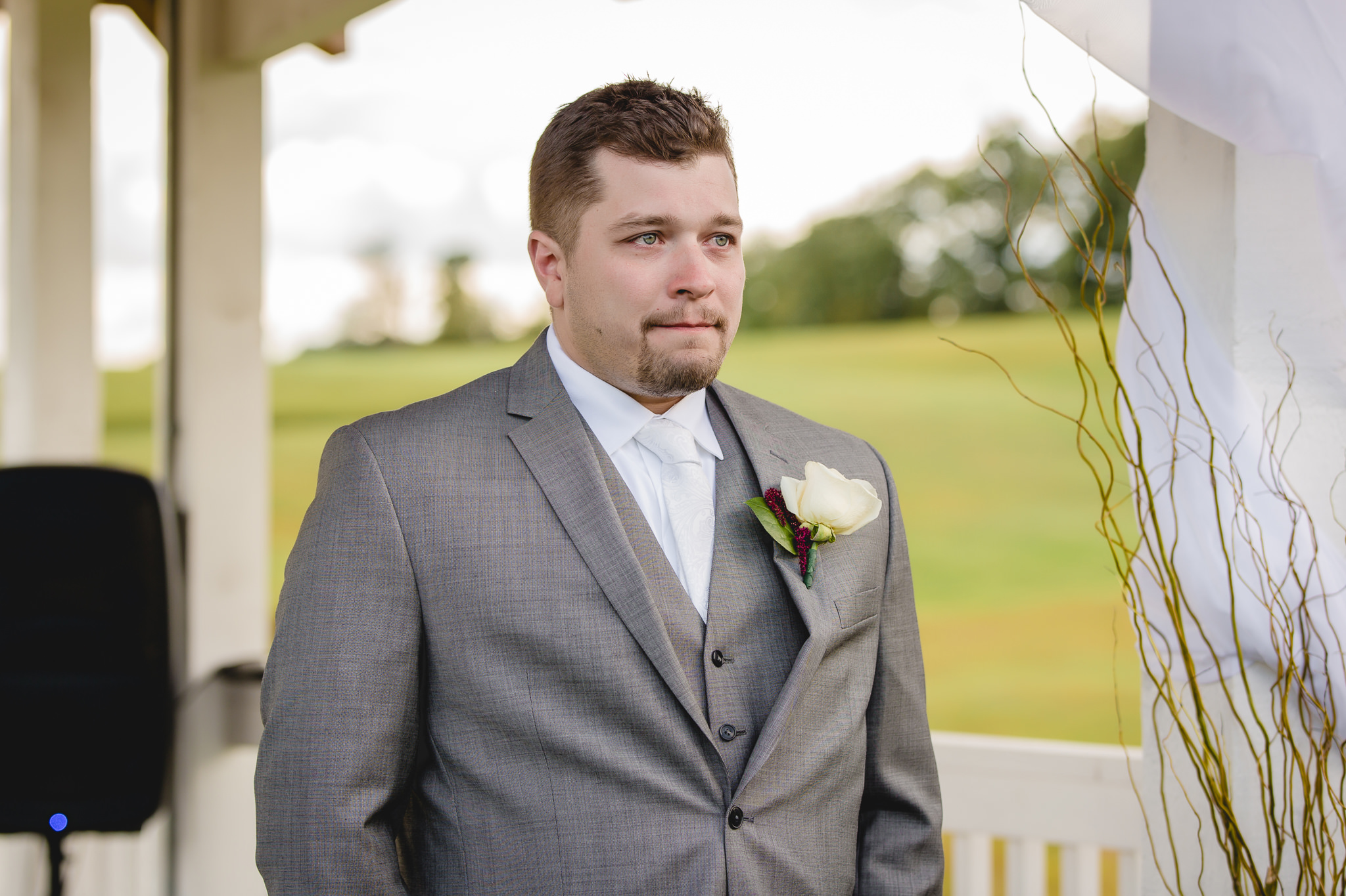 Groom watches his bride walk down the aisle at White Barn