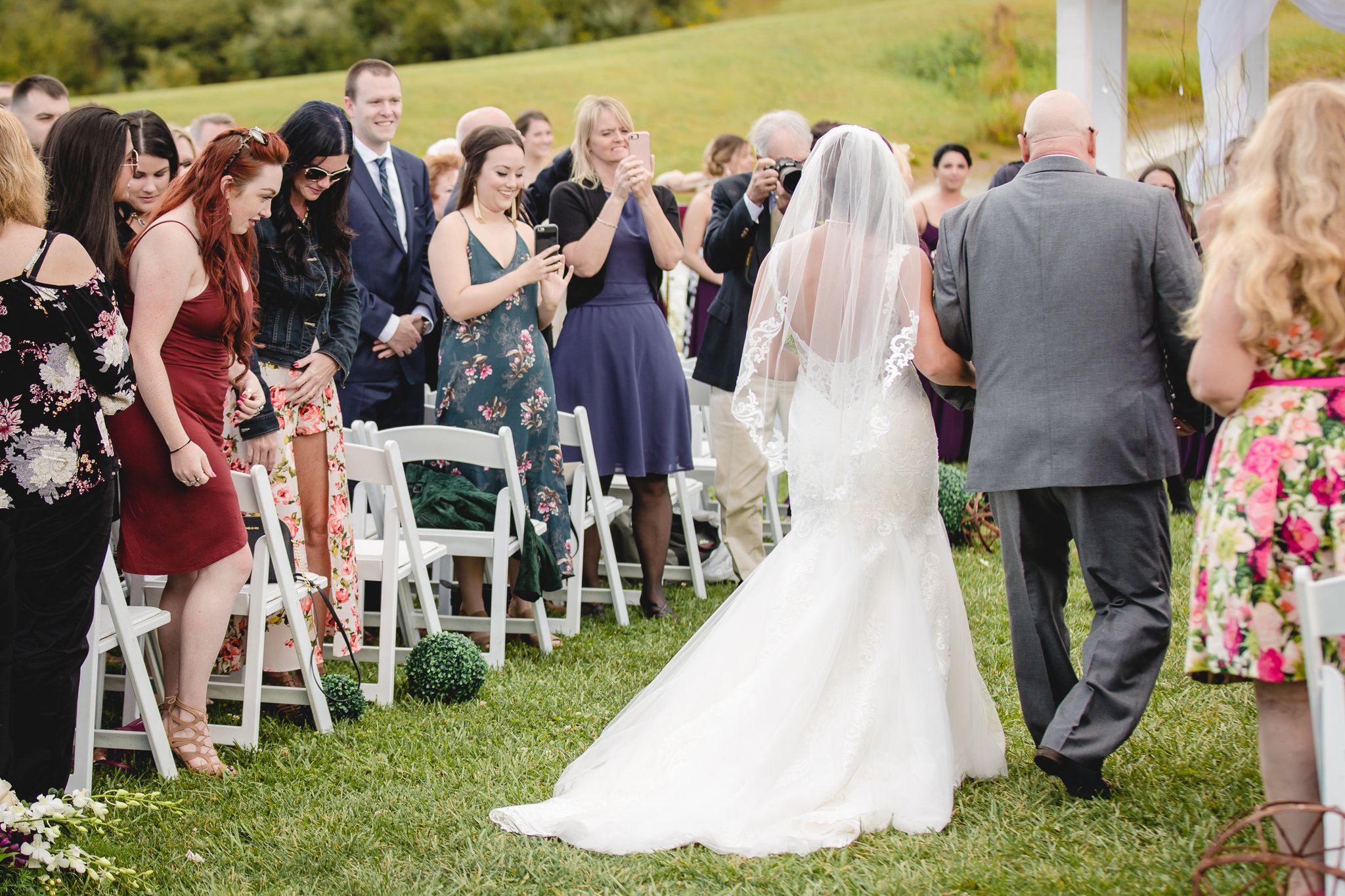 Father and daughter walk down the aisle at a White Barn wedding ceremony
