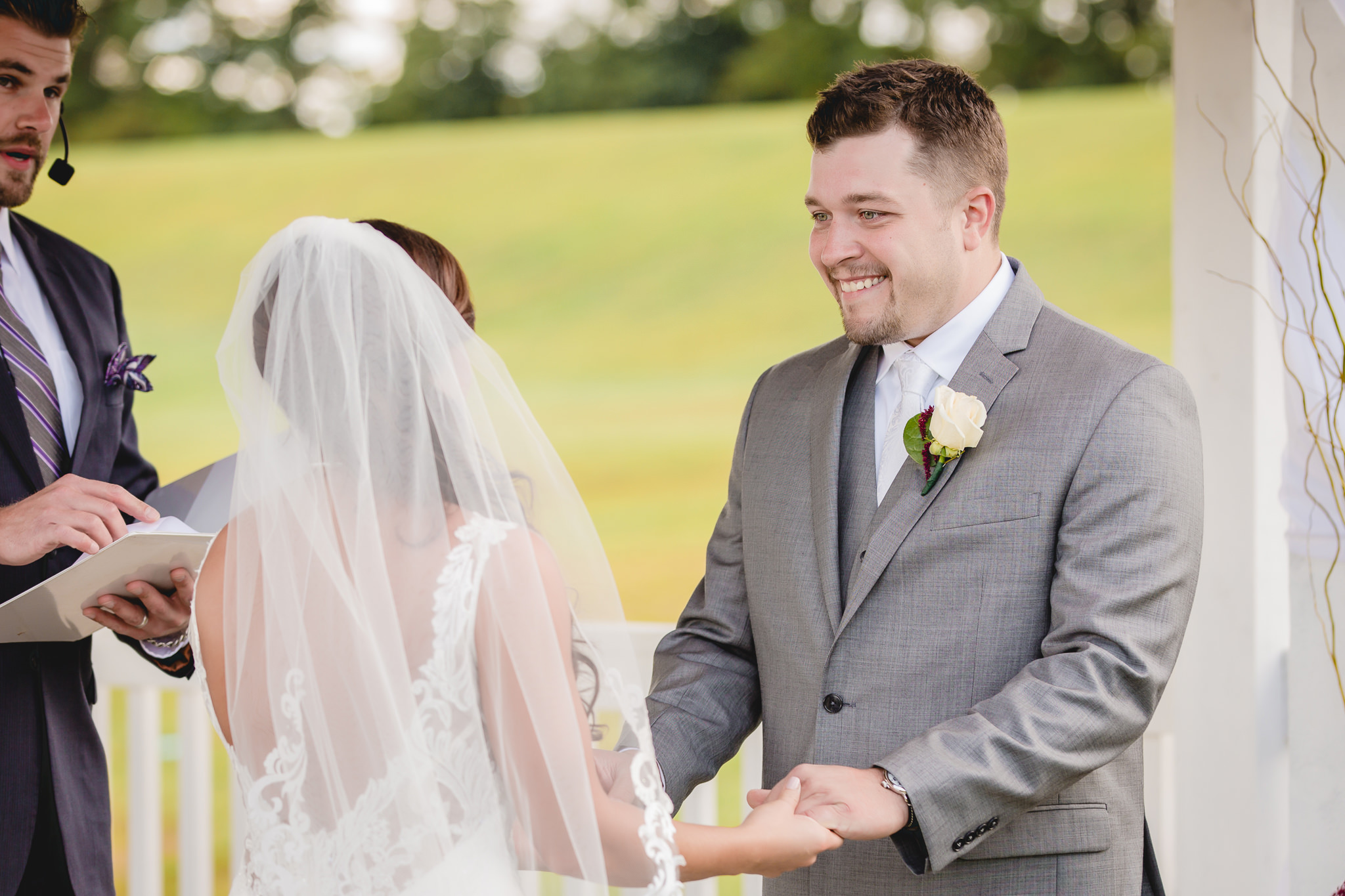 Groom smiles at his bride during a White Barn wedding ceremony