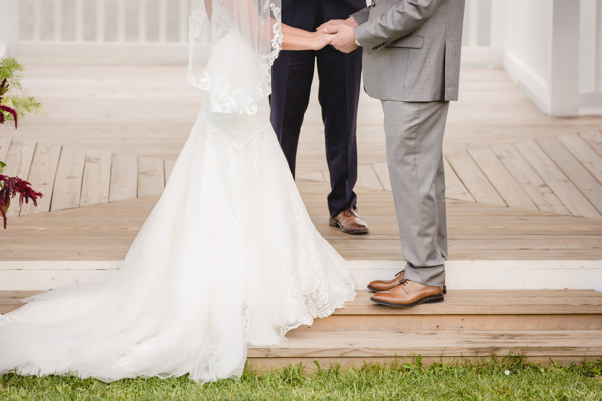 Bride and groom holding hands during their White Barn wedding ceremony