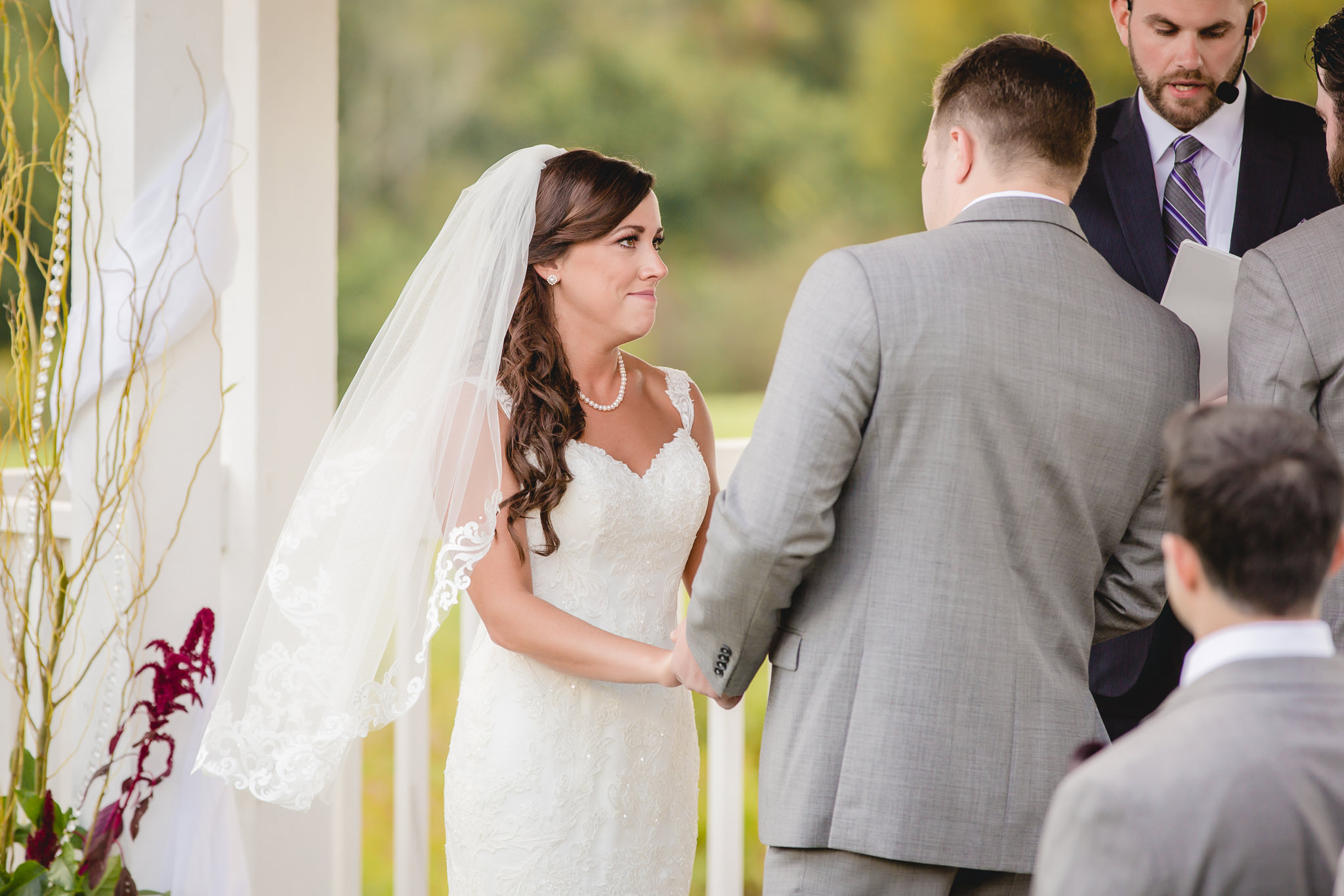 Bride smiles at her groom during their outdoor wedding ceremony at White Barn