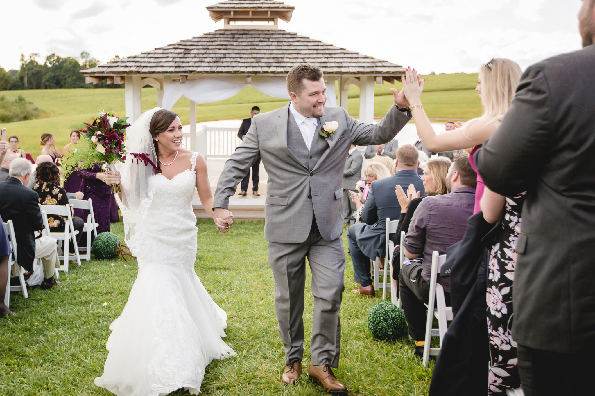 Groom high fives guests after his wedding ceremony at White Barn