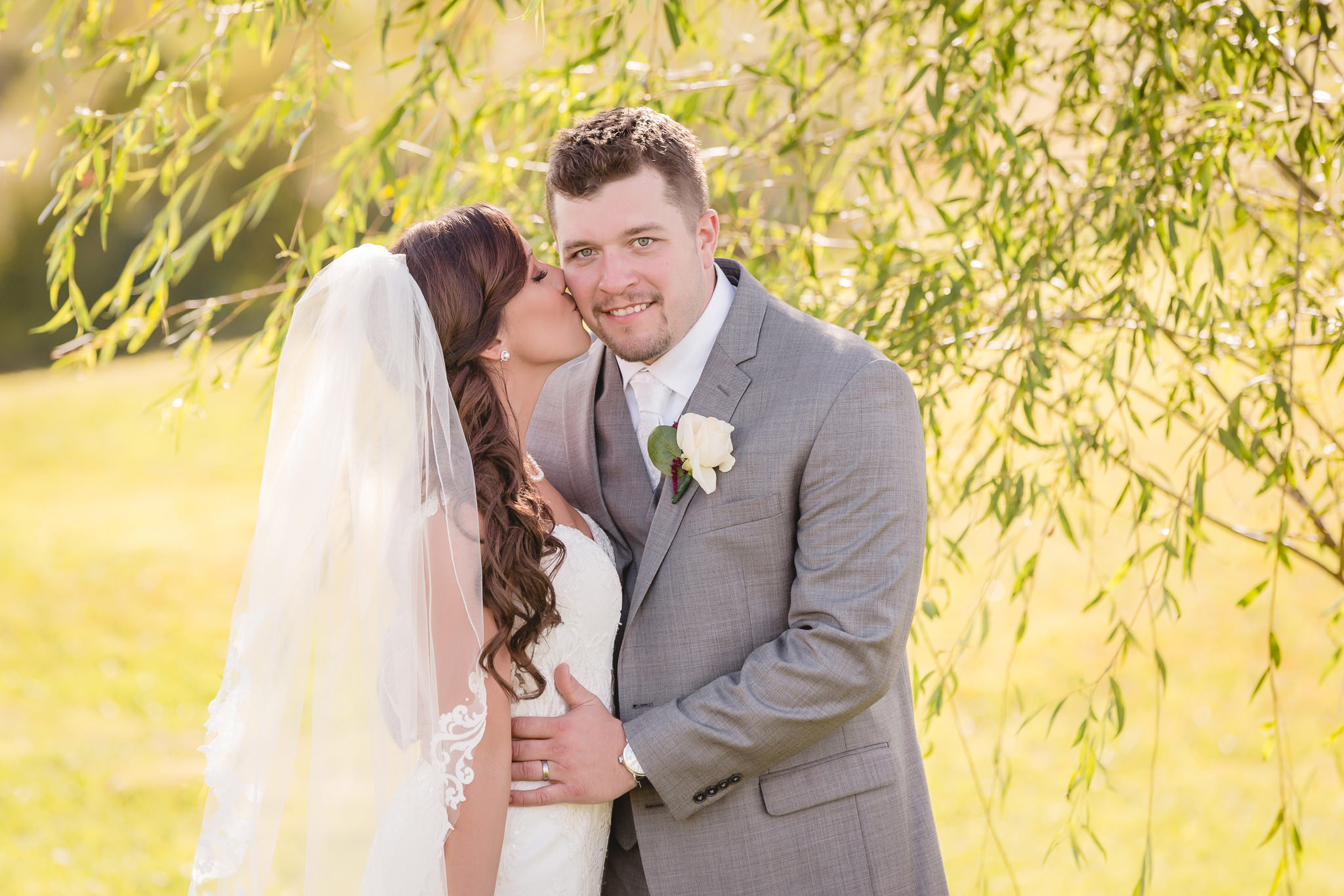 Bride kisses her groom at their White Barn wedding