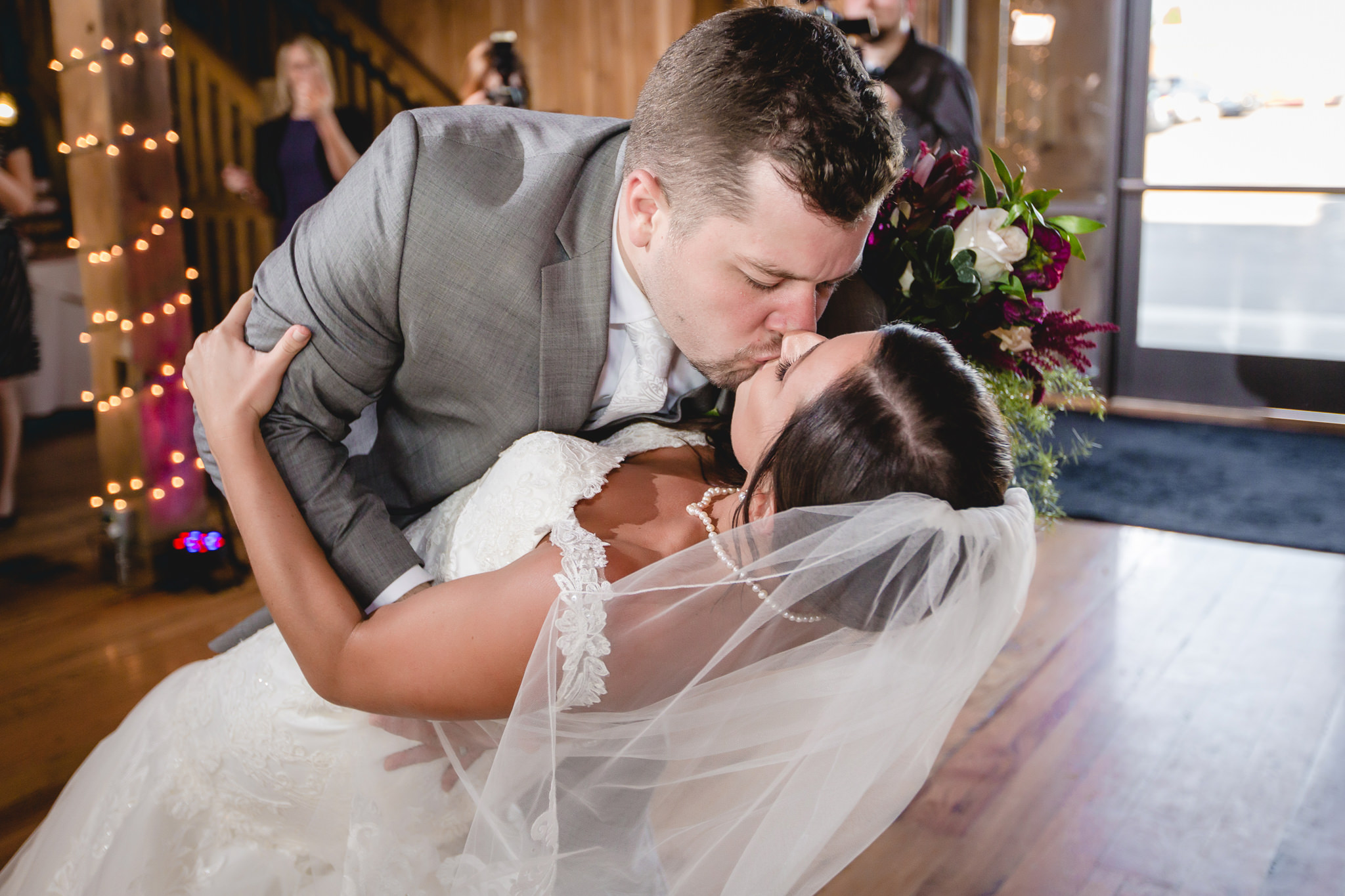 Groom dips his bride for a kiss at White Barn