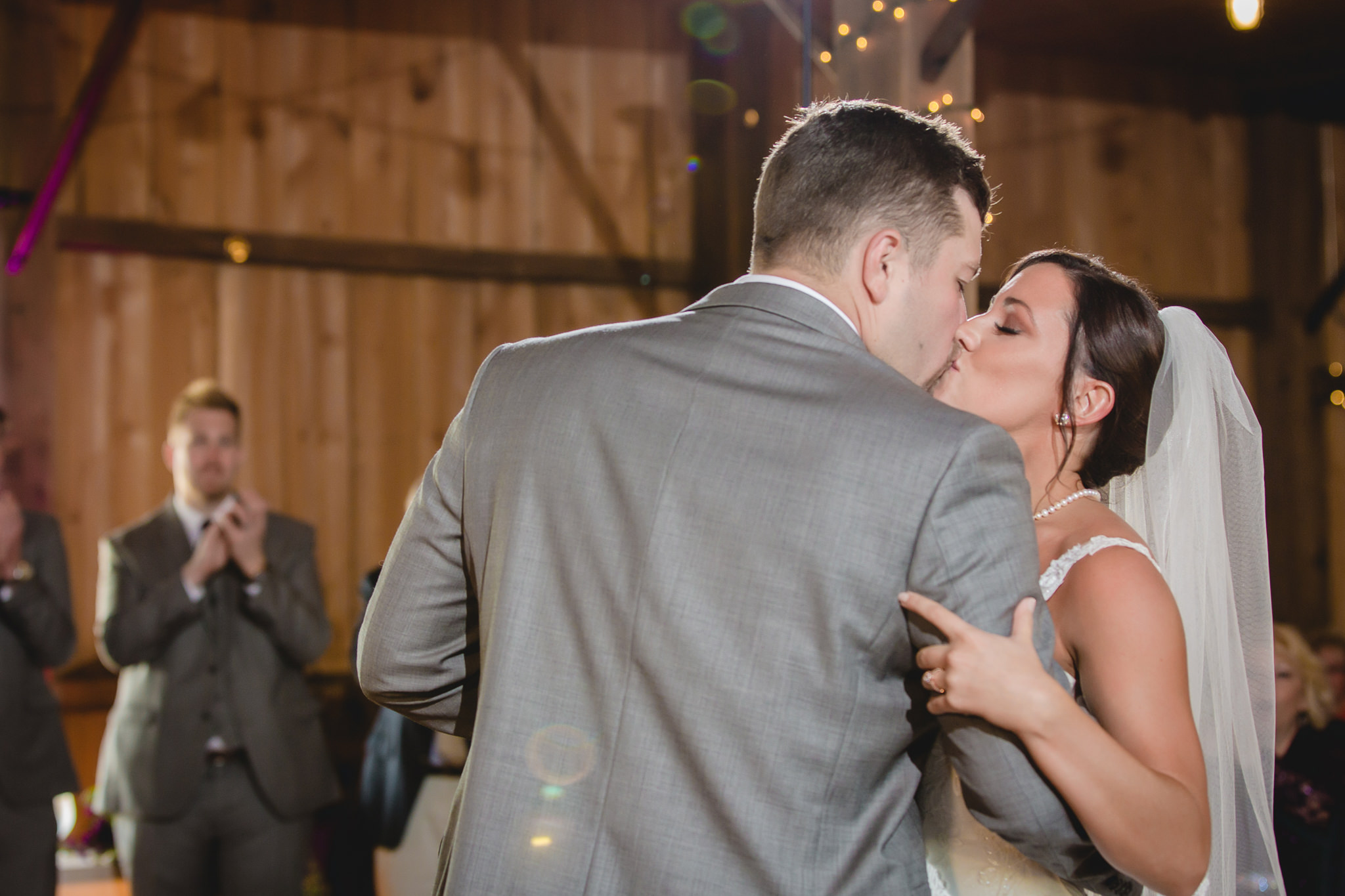 Bride and groom kiss during their first dance at White Barn