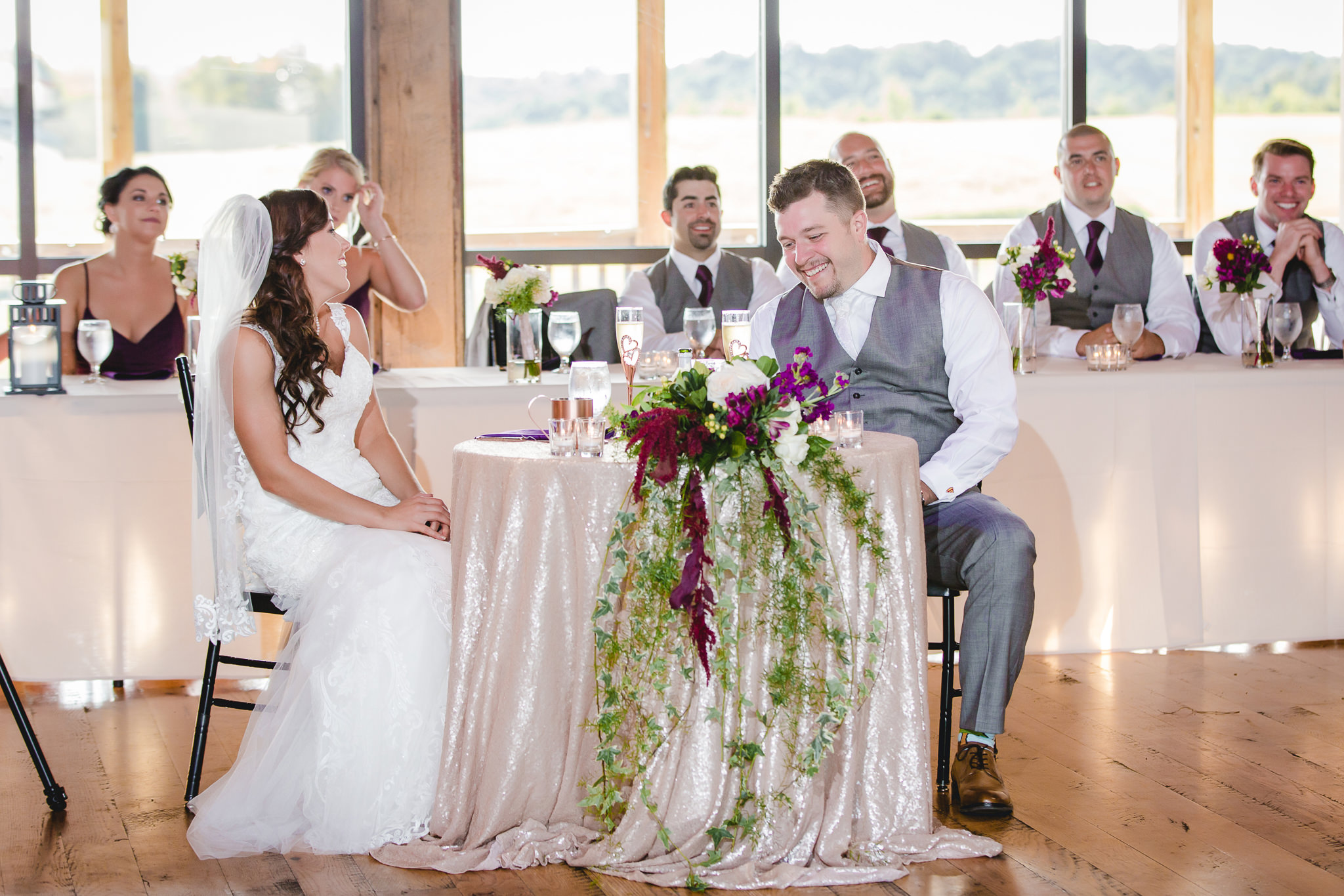 Bride and groom laugh during speeches at White Barn