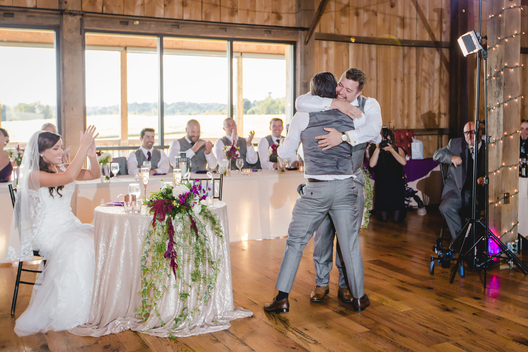 Groom hugs his best man at White Barn wedding reception