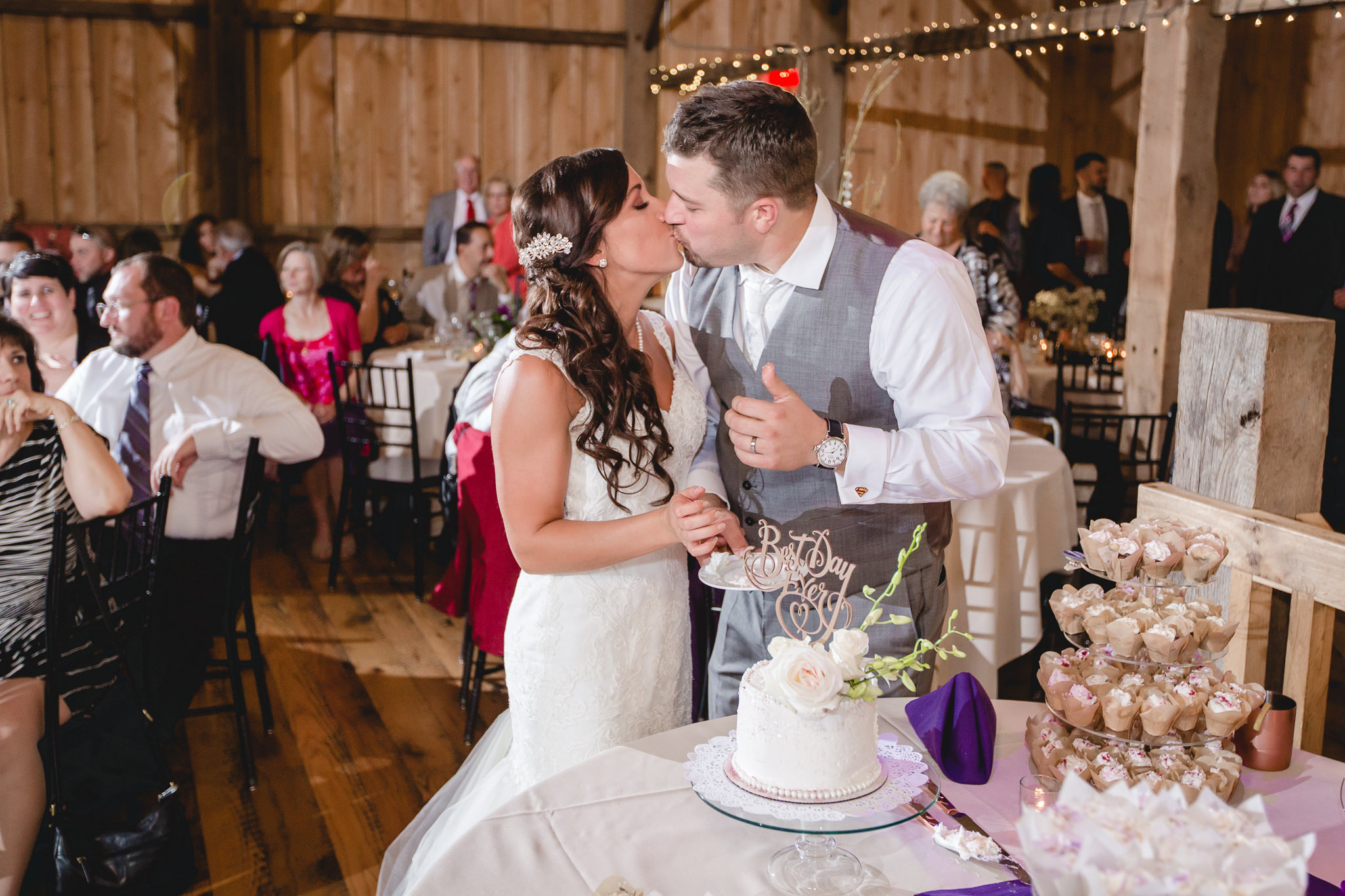 Bride and groom kiss after cutting cake at White Barn