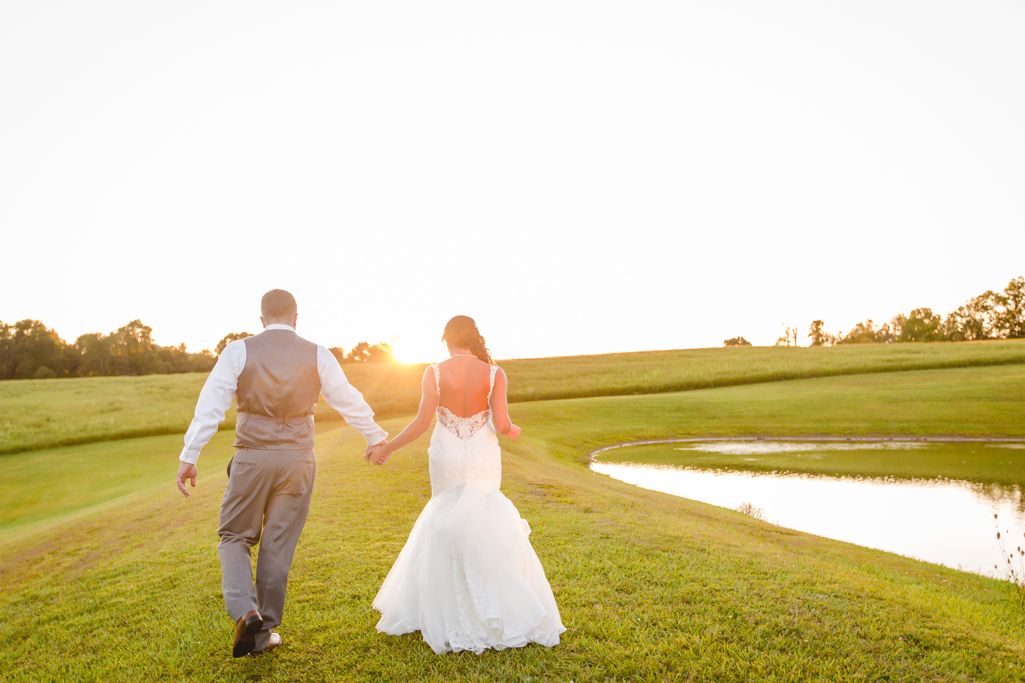 Bride and groom walk towards the sunset by the pond at White Barn
