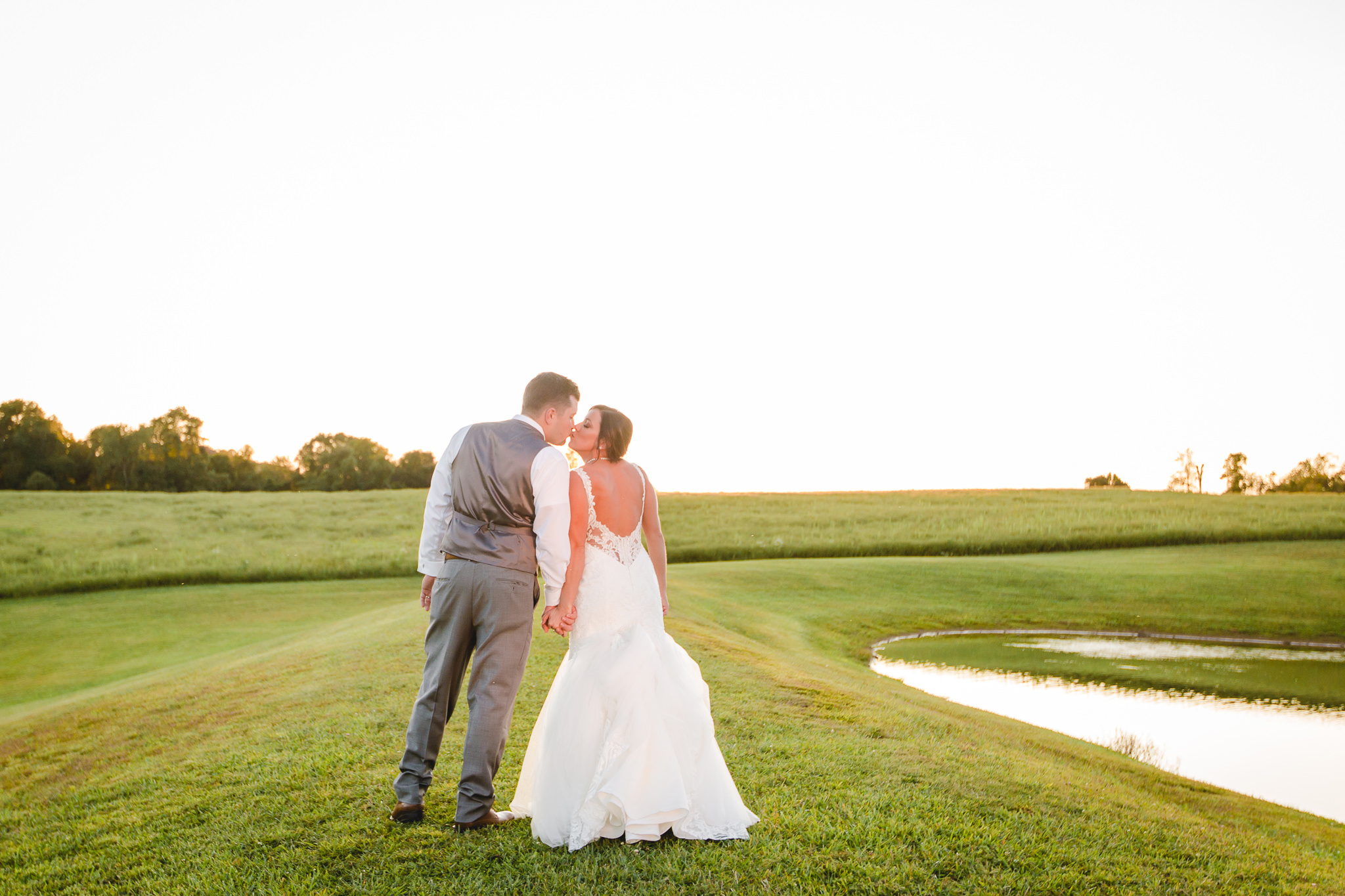Bride and groom kiss by the pond at sunset at White Barn
