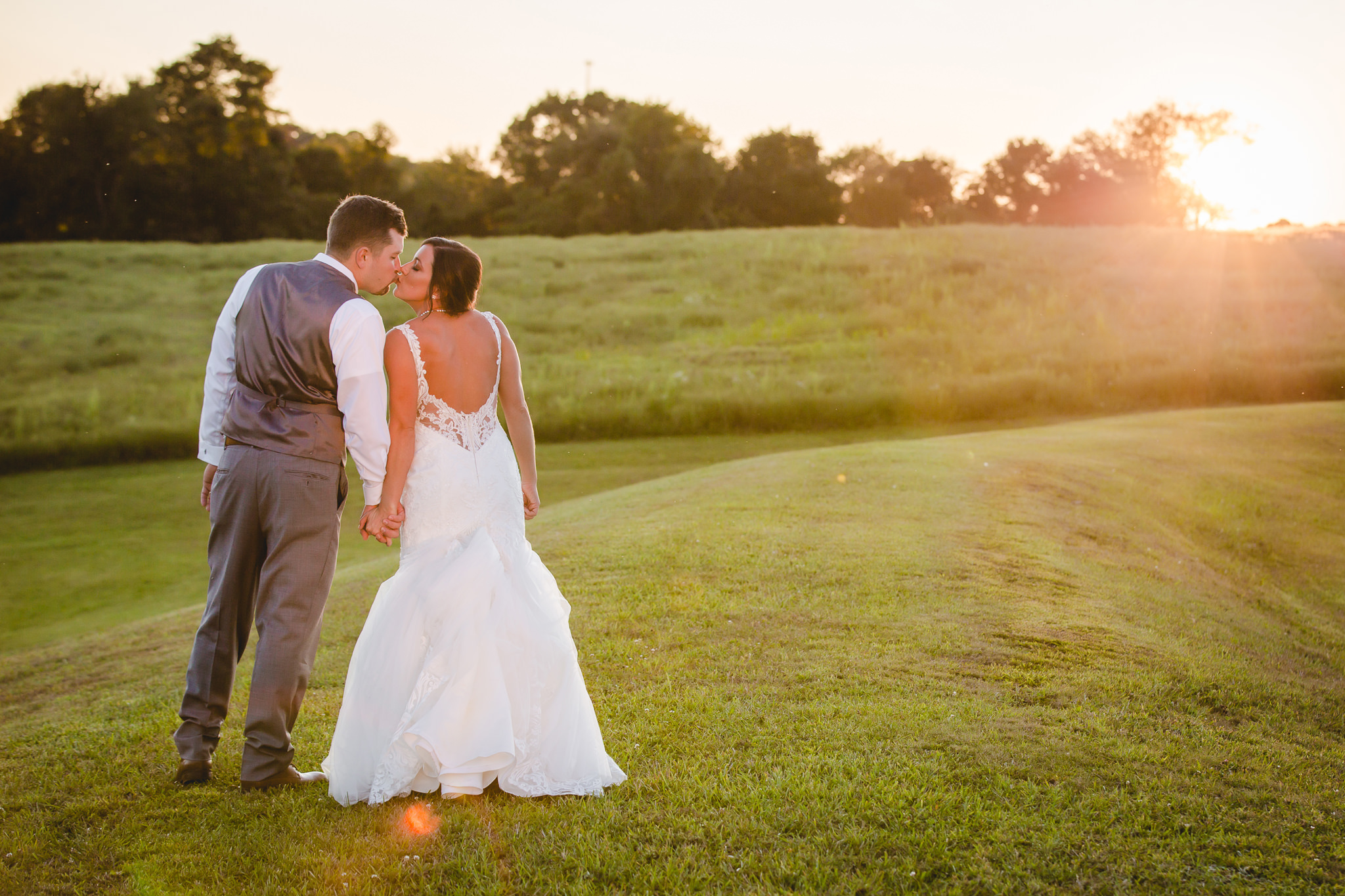Bride and groom kiss during sunset at White Barn