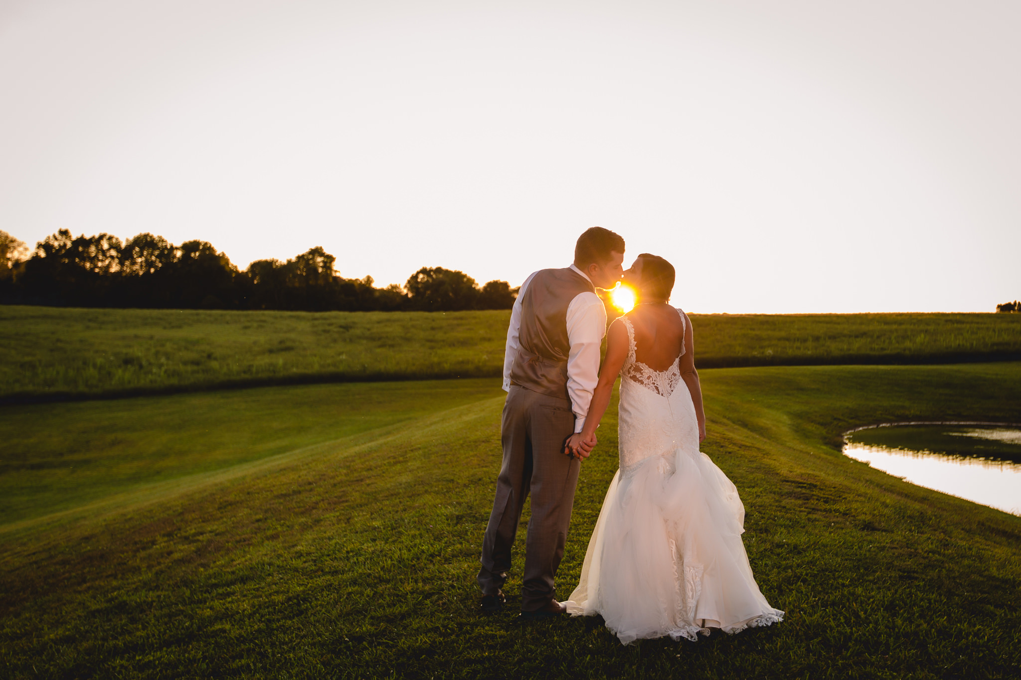 Sun sets as the bride and groom kiss at their White Barn wedding